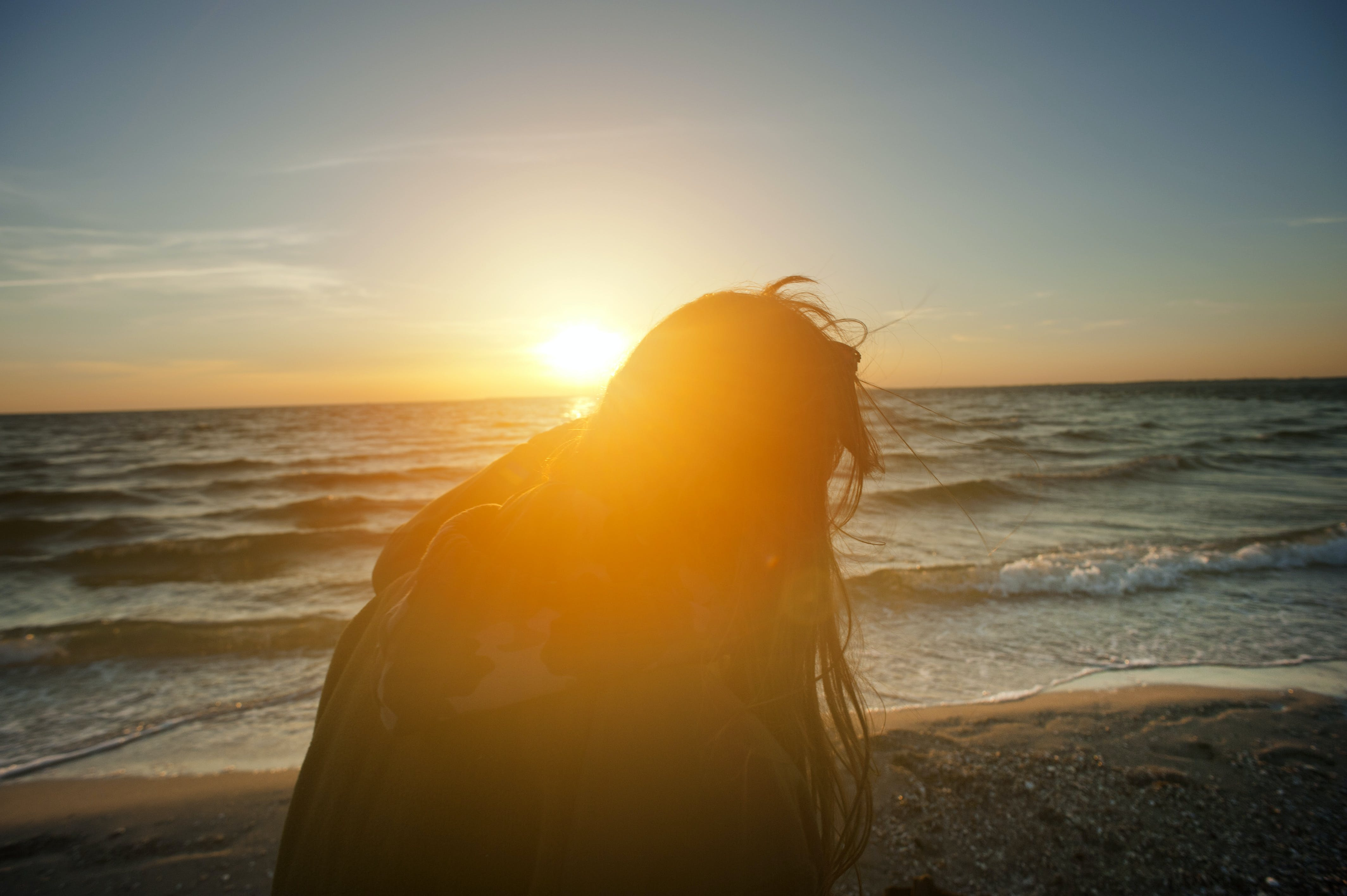 Silhouette of Woman Sitting on Beach Shore