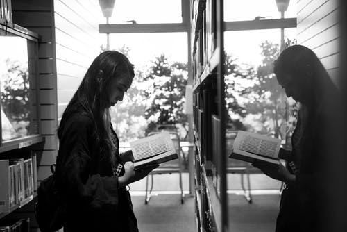 Greyscale Photo of Girl Reading a Book Reflecting on a Glass