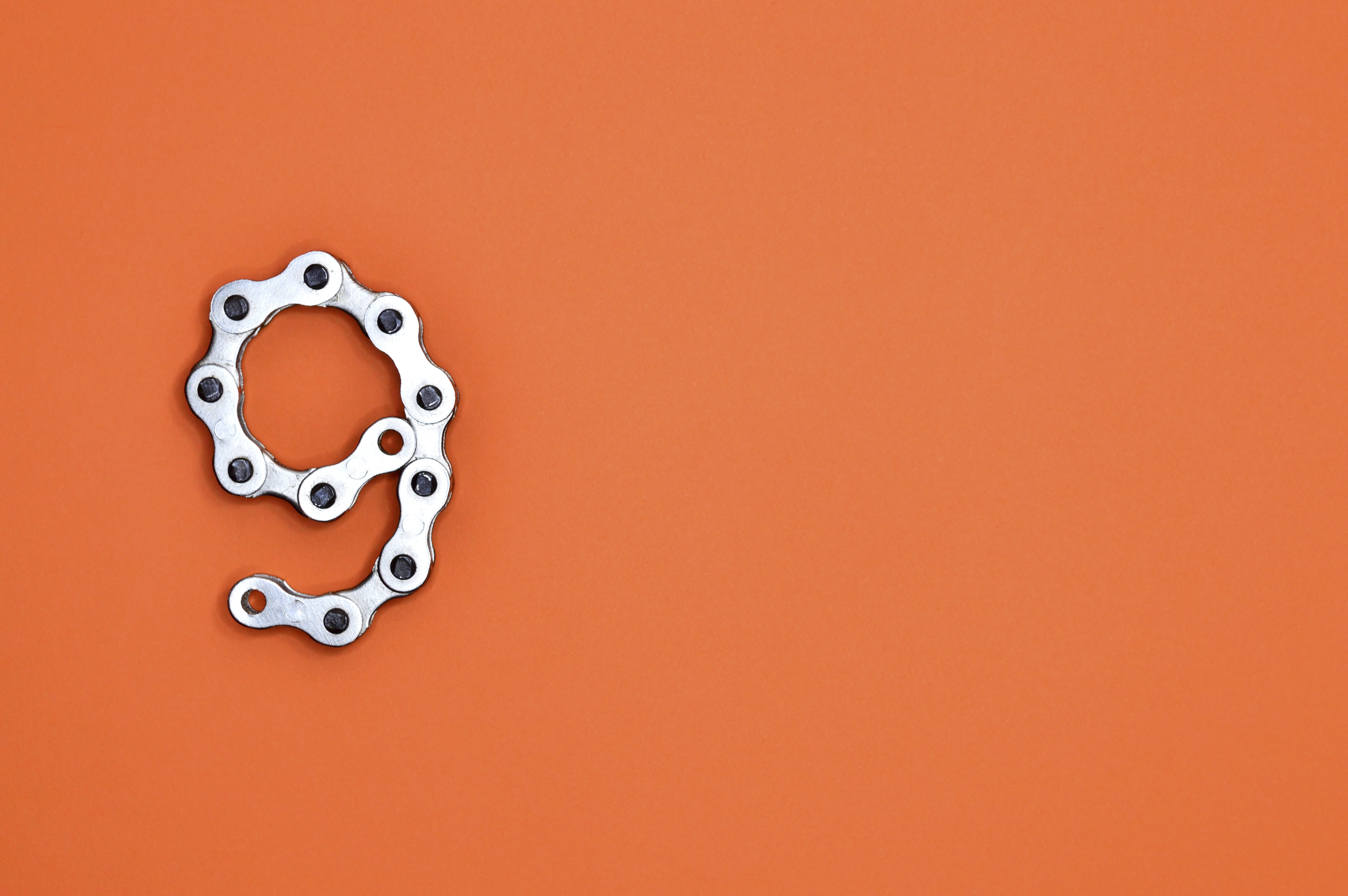 Gray Bicycle Chain on Orange Surface