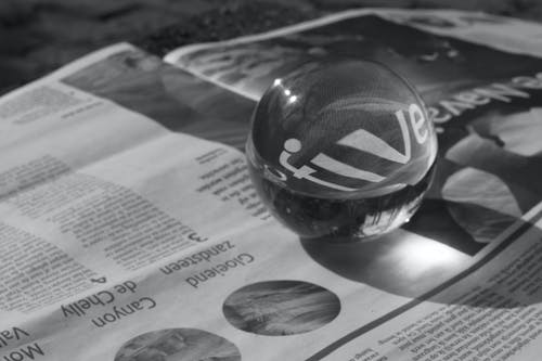 Grayscale Photography of Round Clear Paper Weight on Newspaper