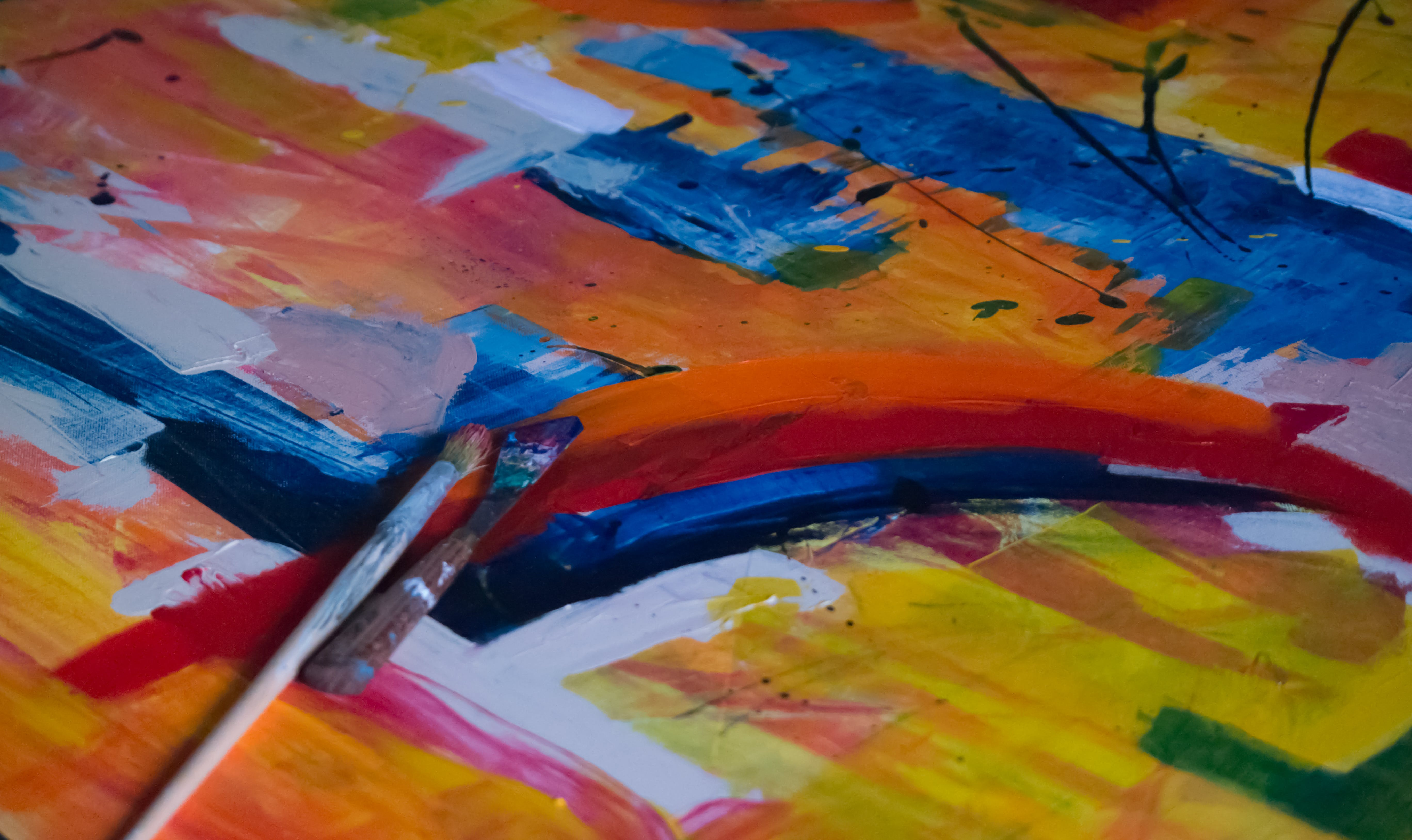 Two Paintbrushes on Multicolored Abstract Painting