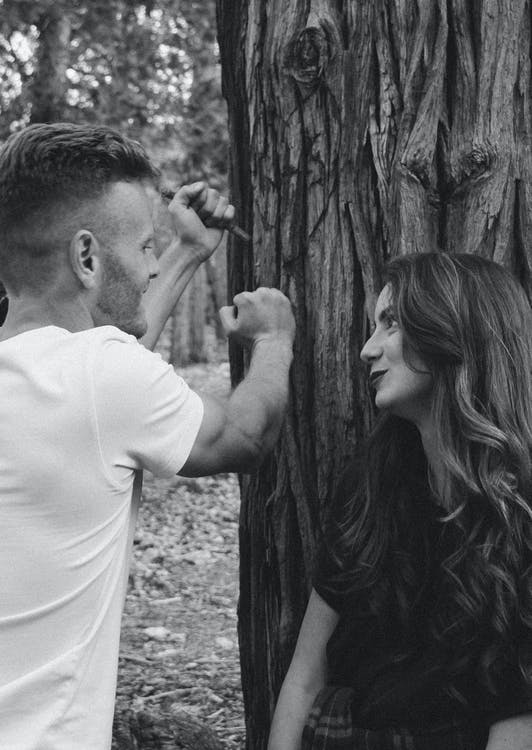 Monochrome Photography of Man and Woman Near Tree