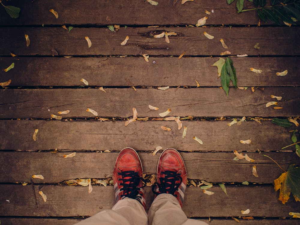 Person Standing on Brown Wooden Deck
