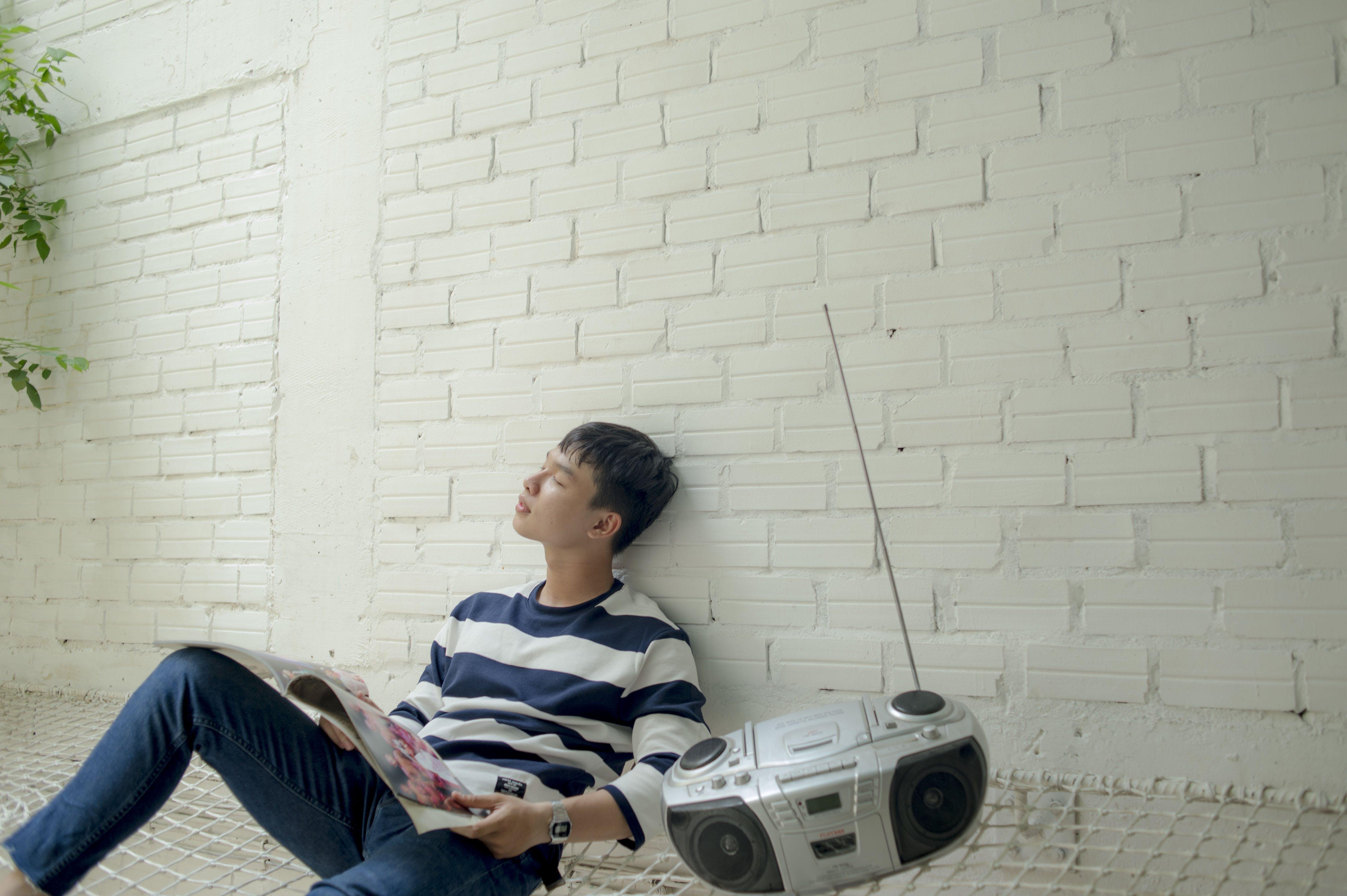 Photo of Man Sitting Near Radio