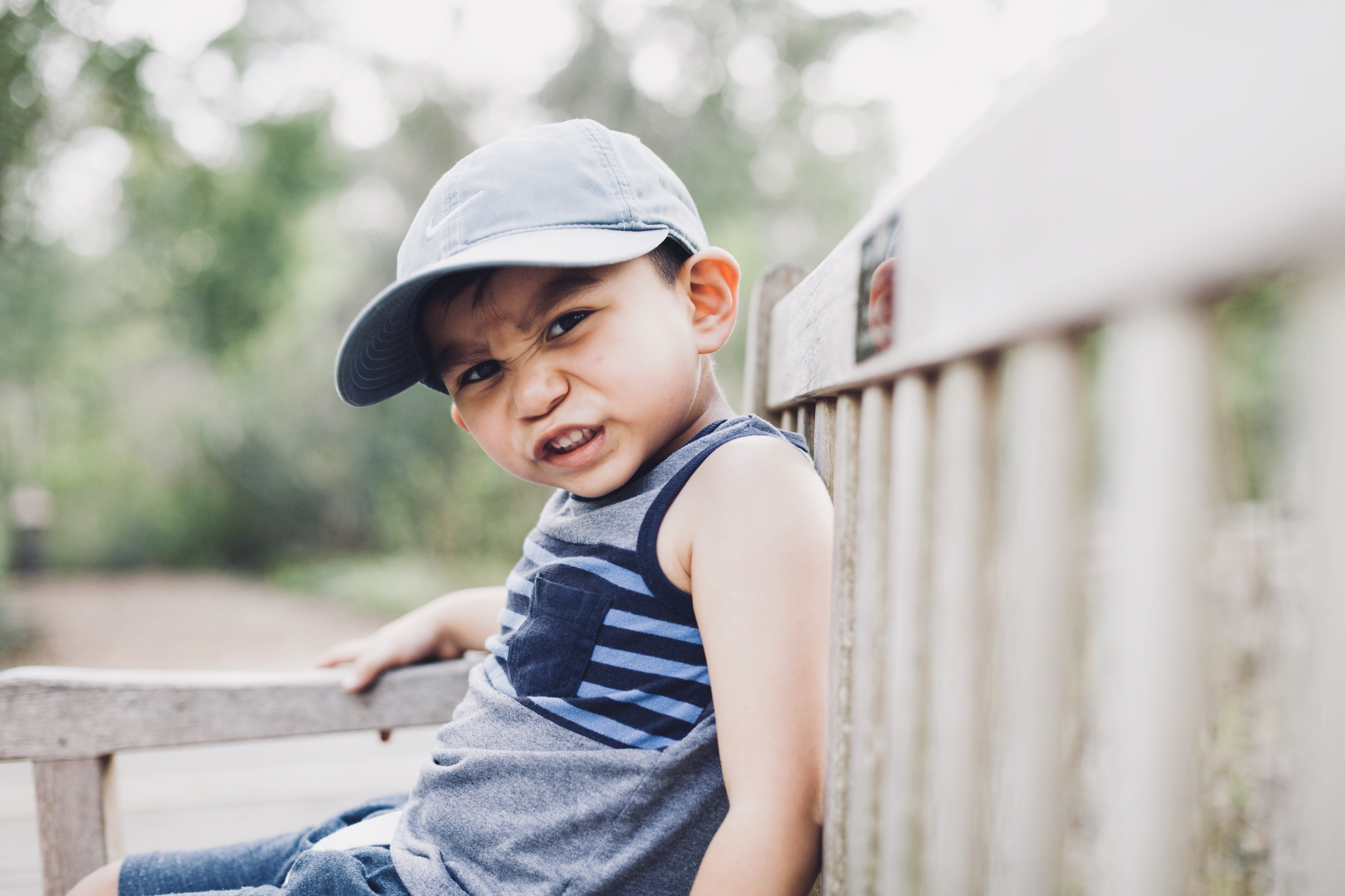Shallow Focus Photography Of A Boy Sitting On Bench