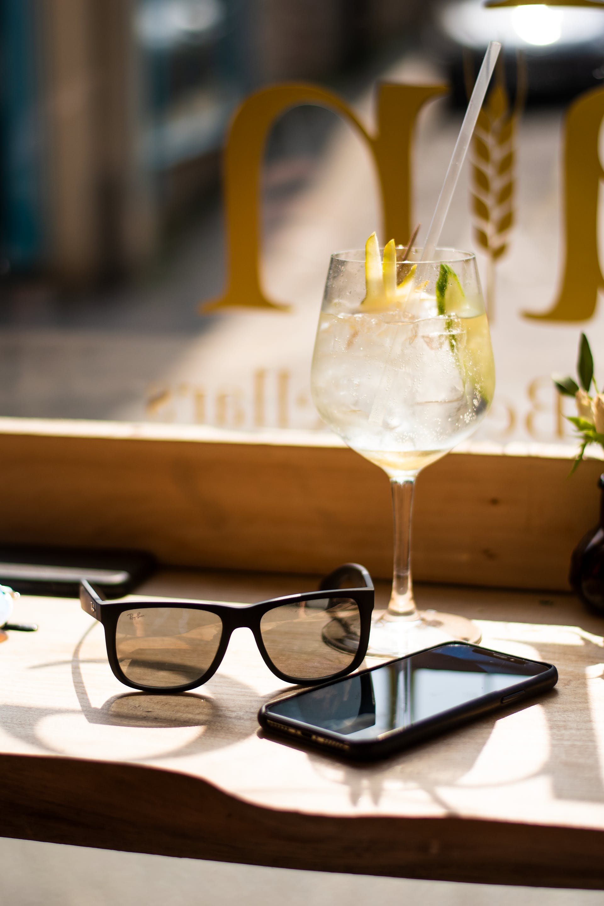 Wine Glass Beside Android Smartphone and Sunglasses