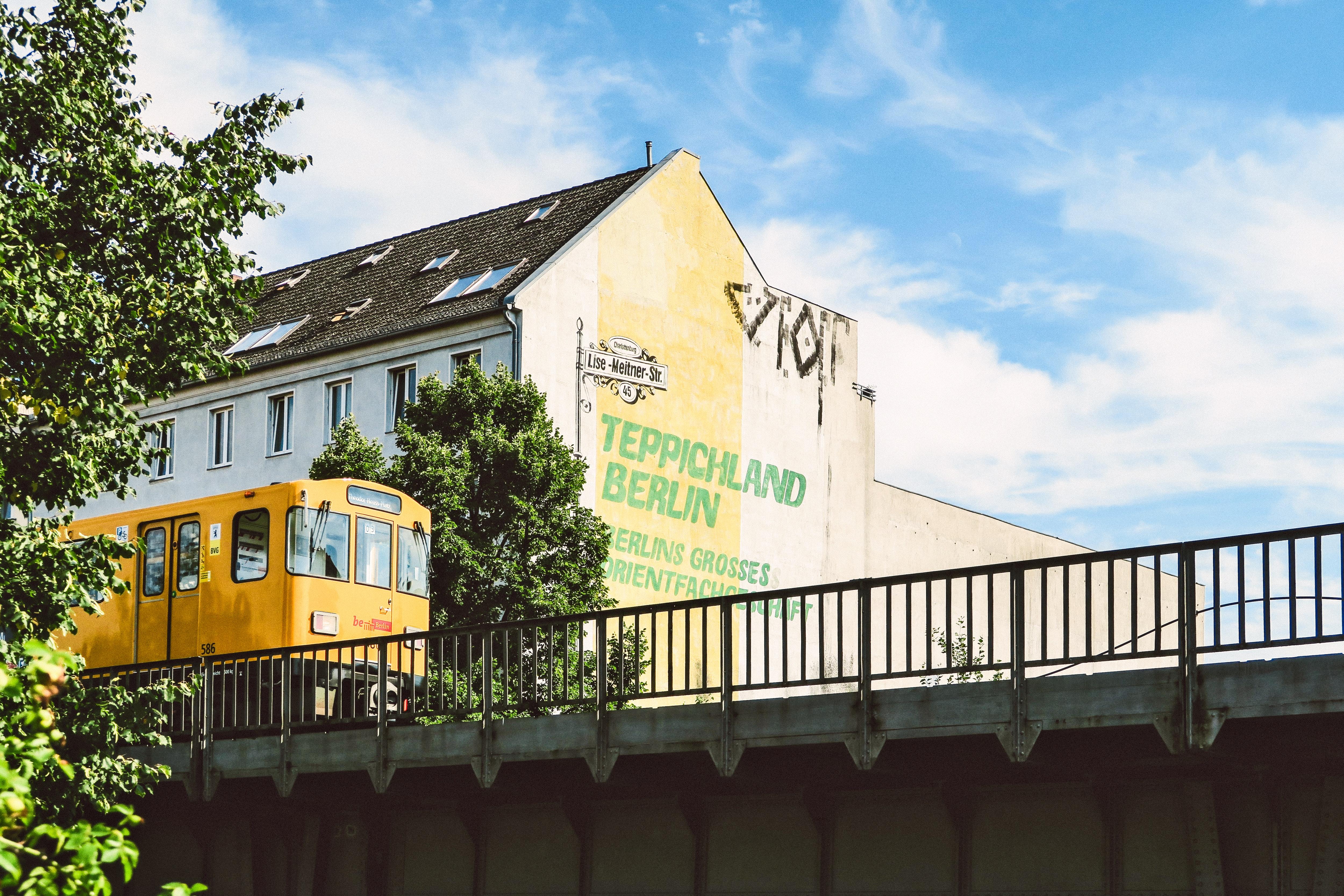 Yellow Train Beside Teppichland Berun Building Free Stock Photo