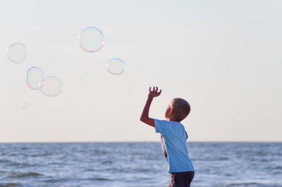 Boy in White T Shirt Playing Bubbles Near Body of Water Under Grey Sky during Daytime