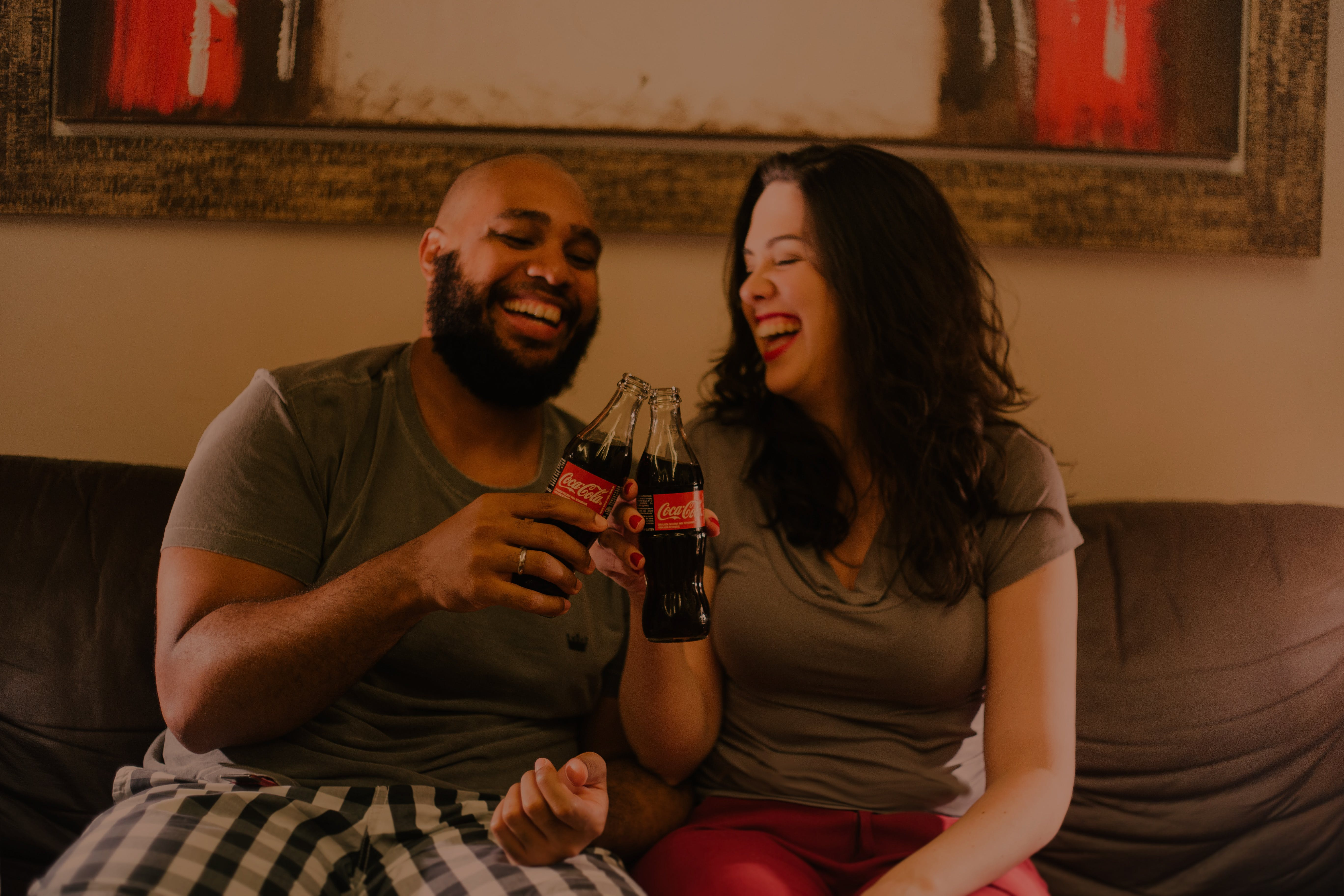 Two Laughing Man and Woman While Holding Coca-cola Glass Bottles