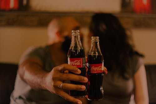 Close-Up Photography of People Holding Coca-Cola Bottles