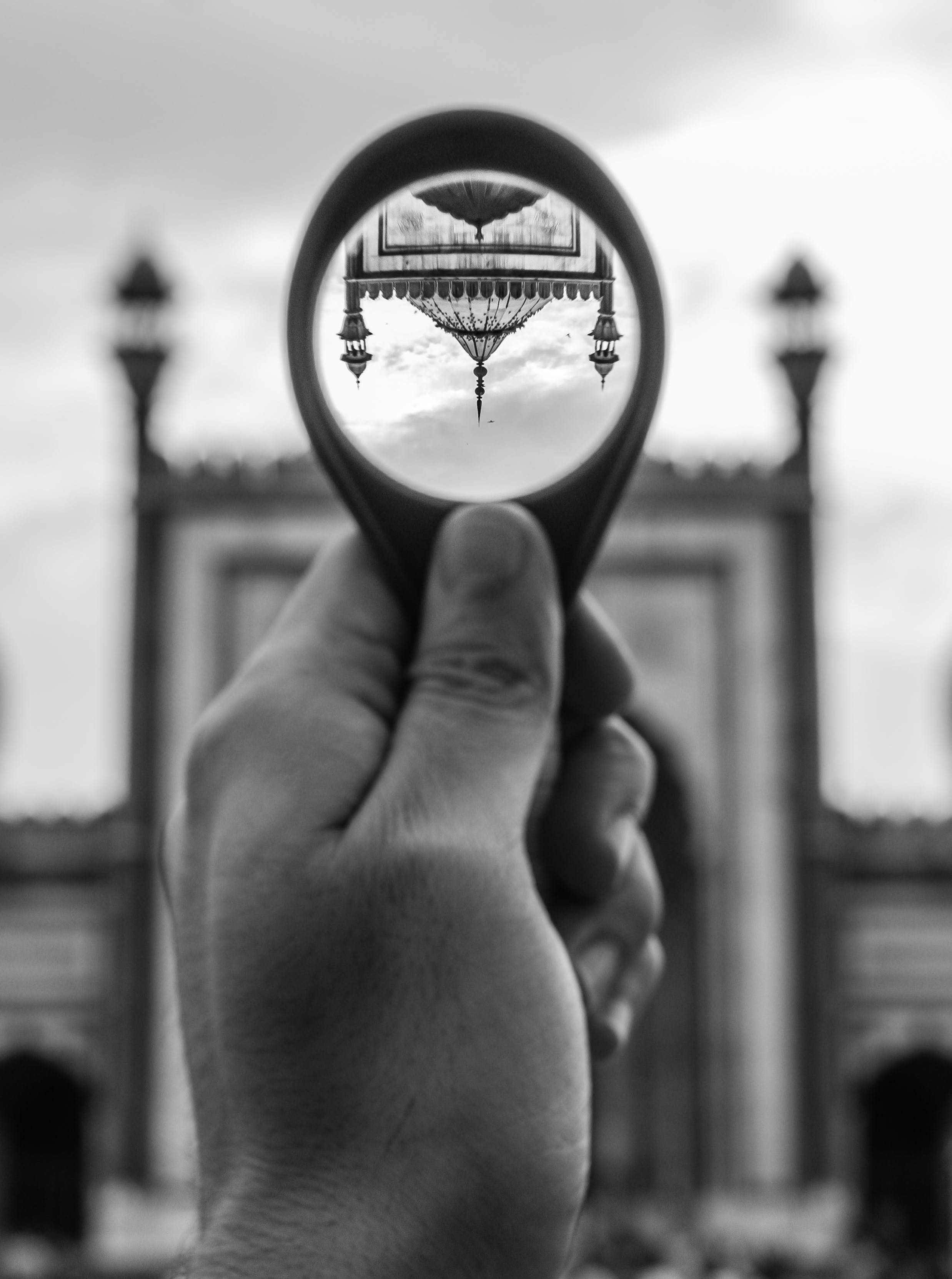 Grayscale Photo of Person Holding Round Magnifying Glass