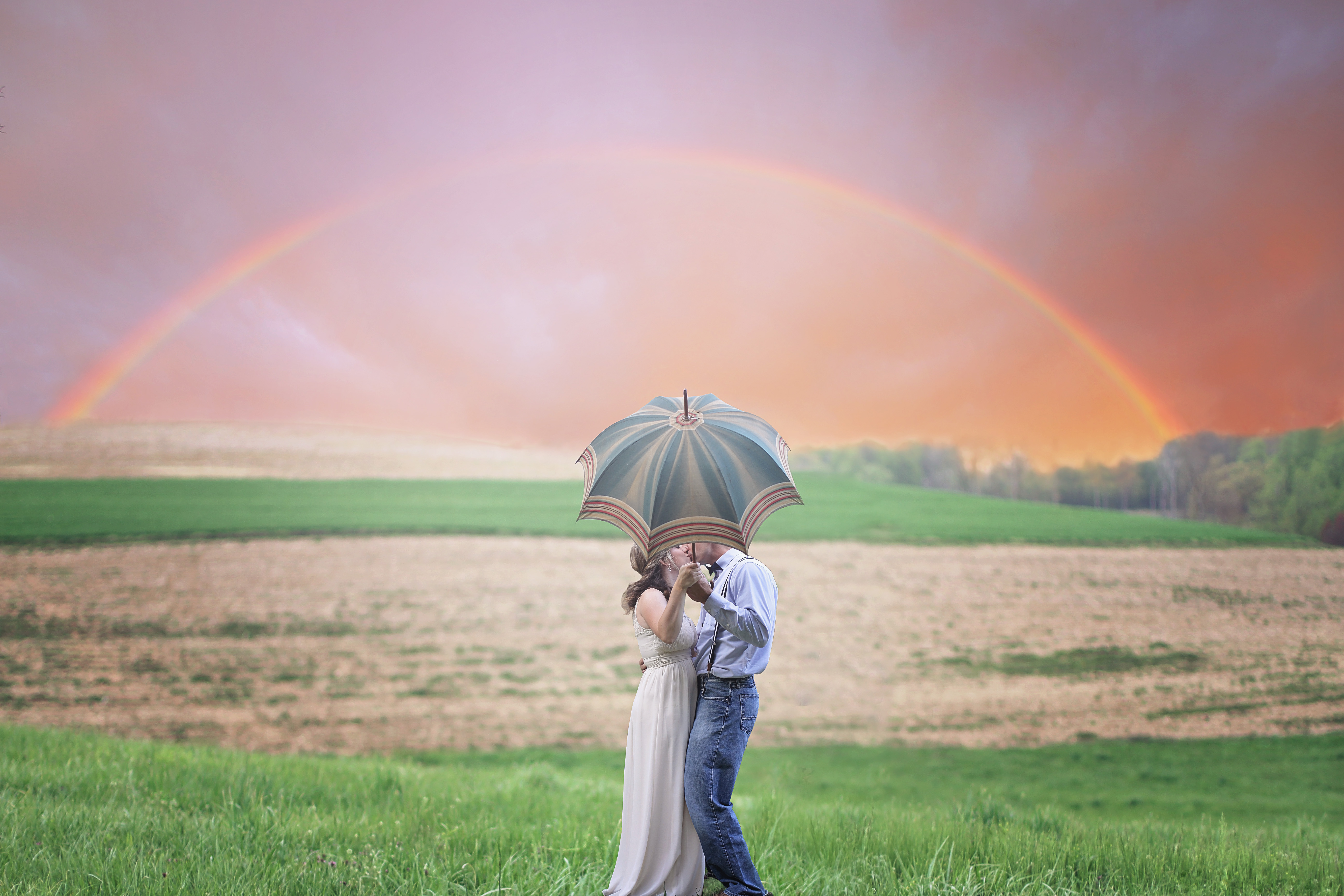 Photo of Couple Holding Umbrella While Kissing