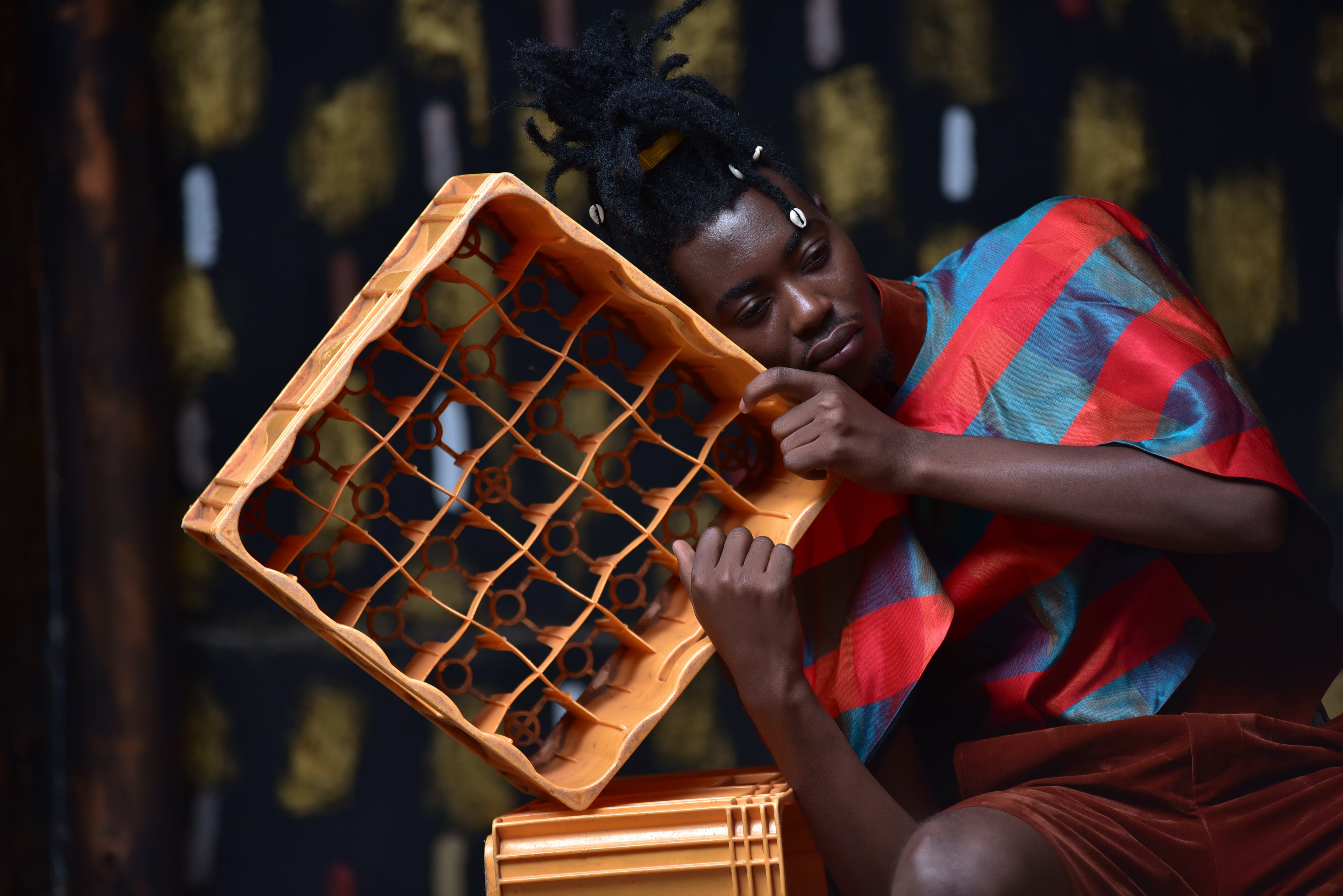 Photography of a Guy Leaning on Plastic Bottle Crate