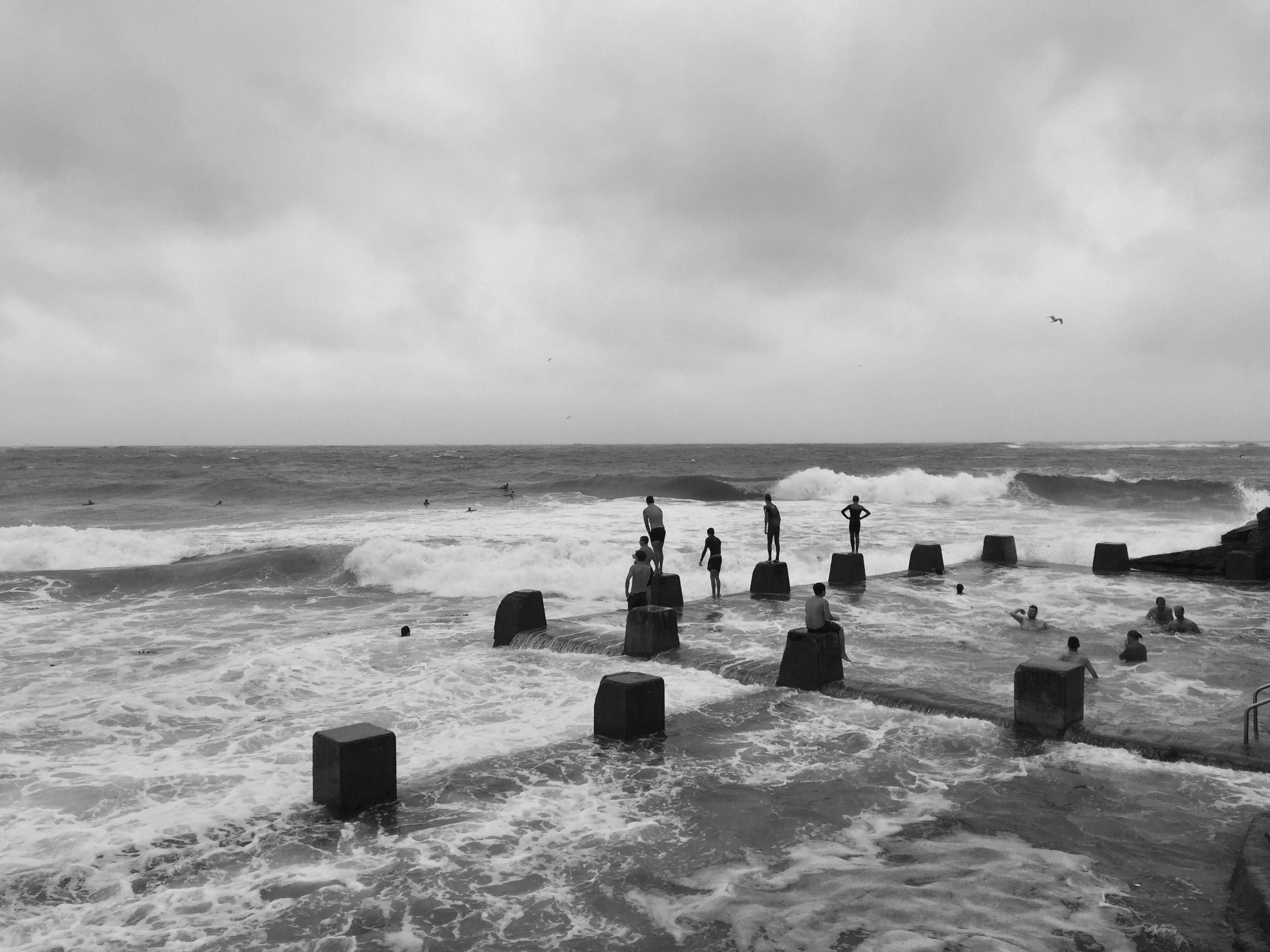 Grayscale Photo of People in Beach