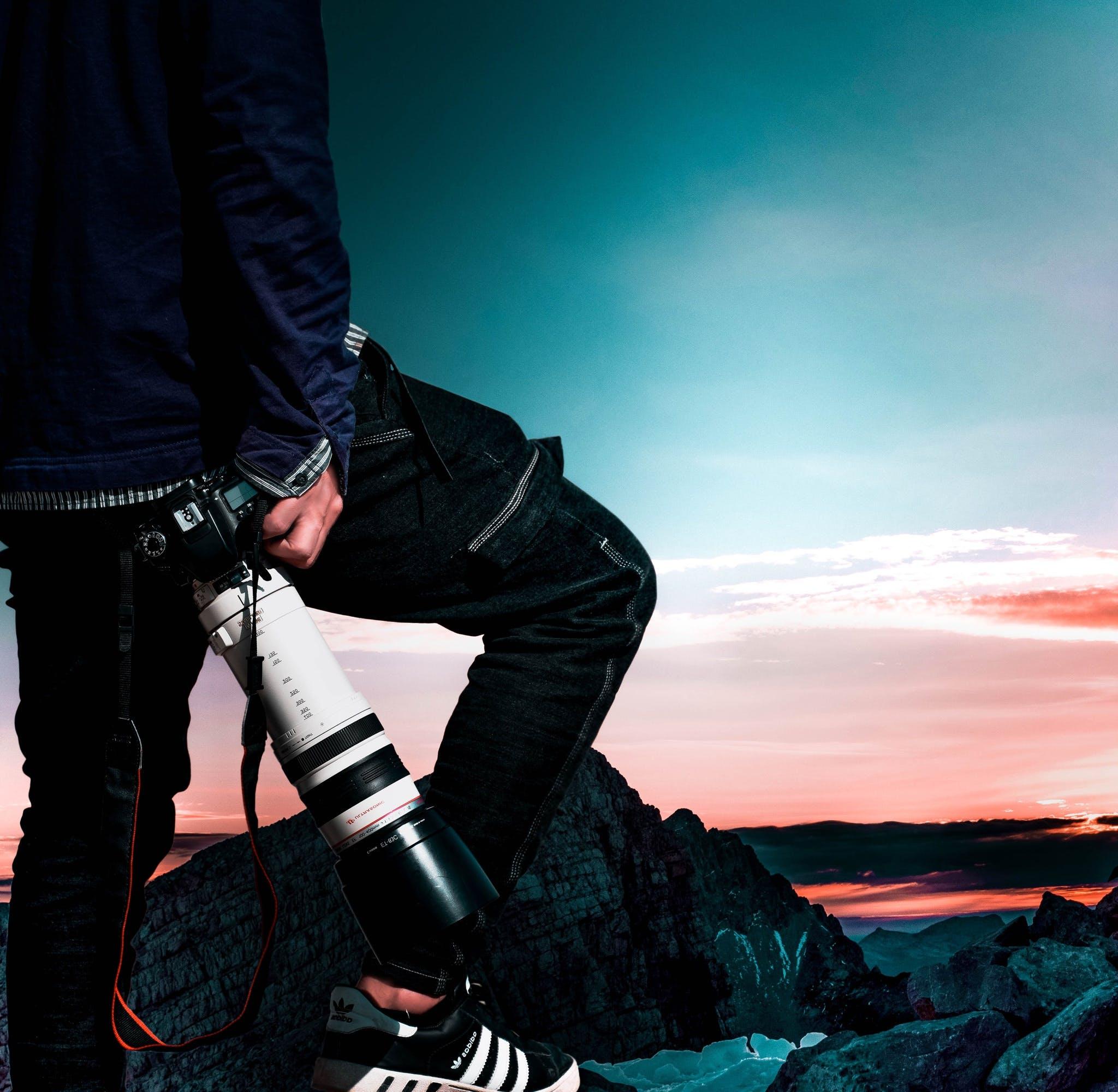 Man Wearing Black Bomber Jacket and Denim Jeans Holding Dslr Camera