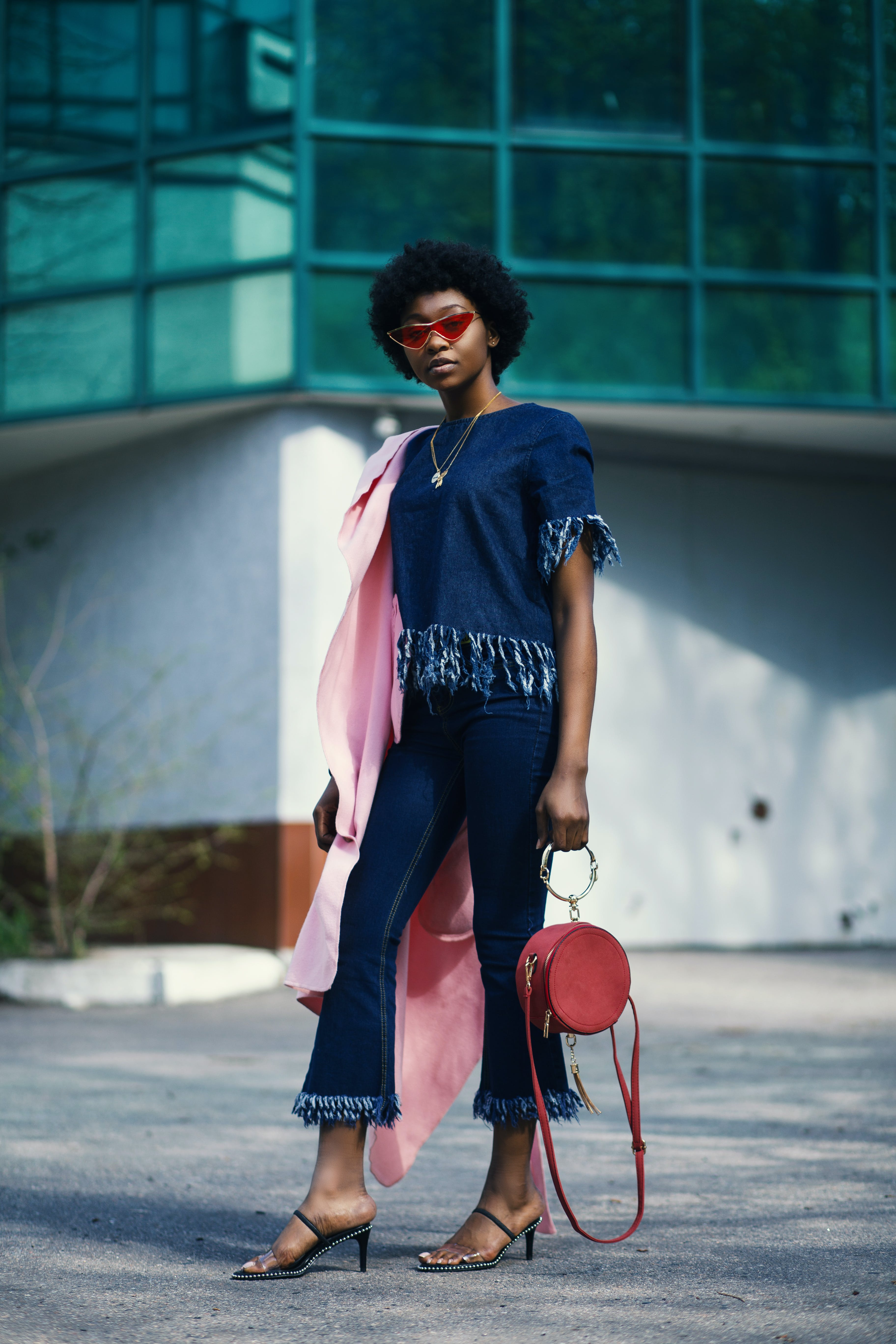 Shallow Focus Photography of Woman in Blue Clothes Holding Red Leather 2-way Handbag