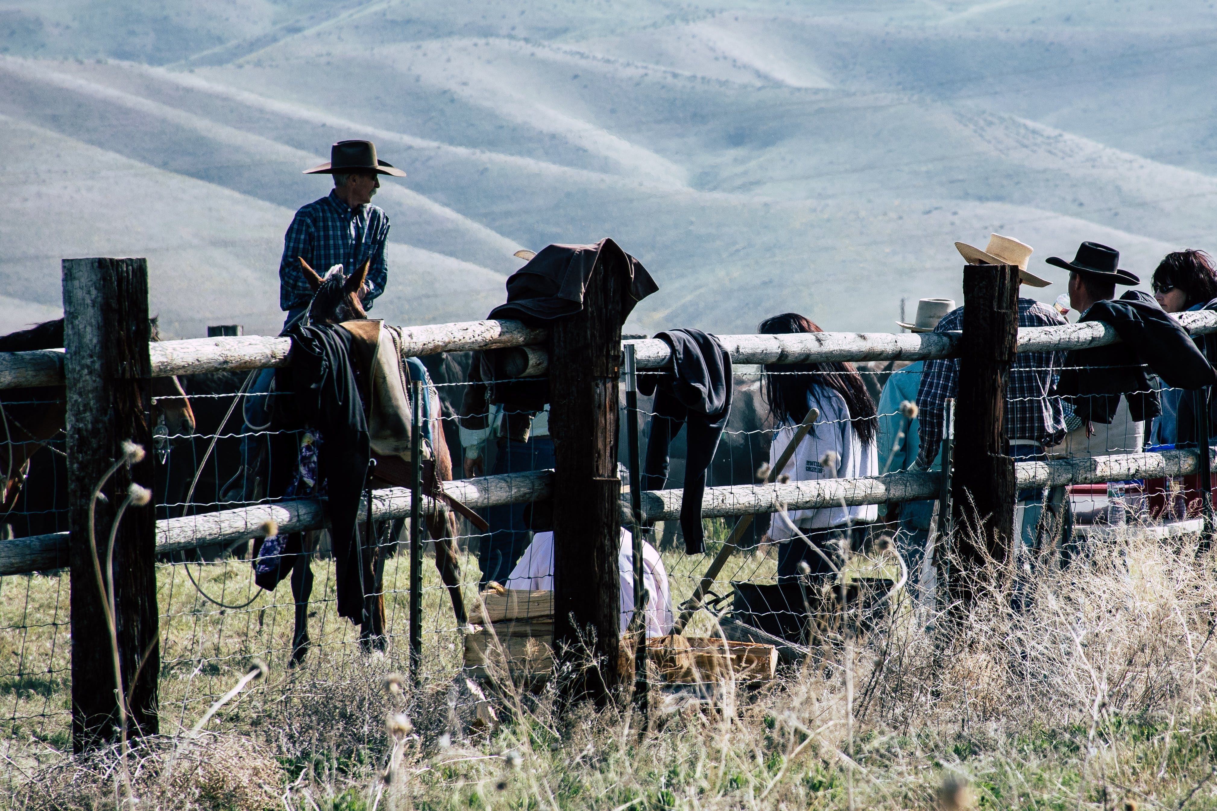 Cowboys Leaning on Brown Fence