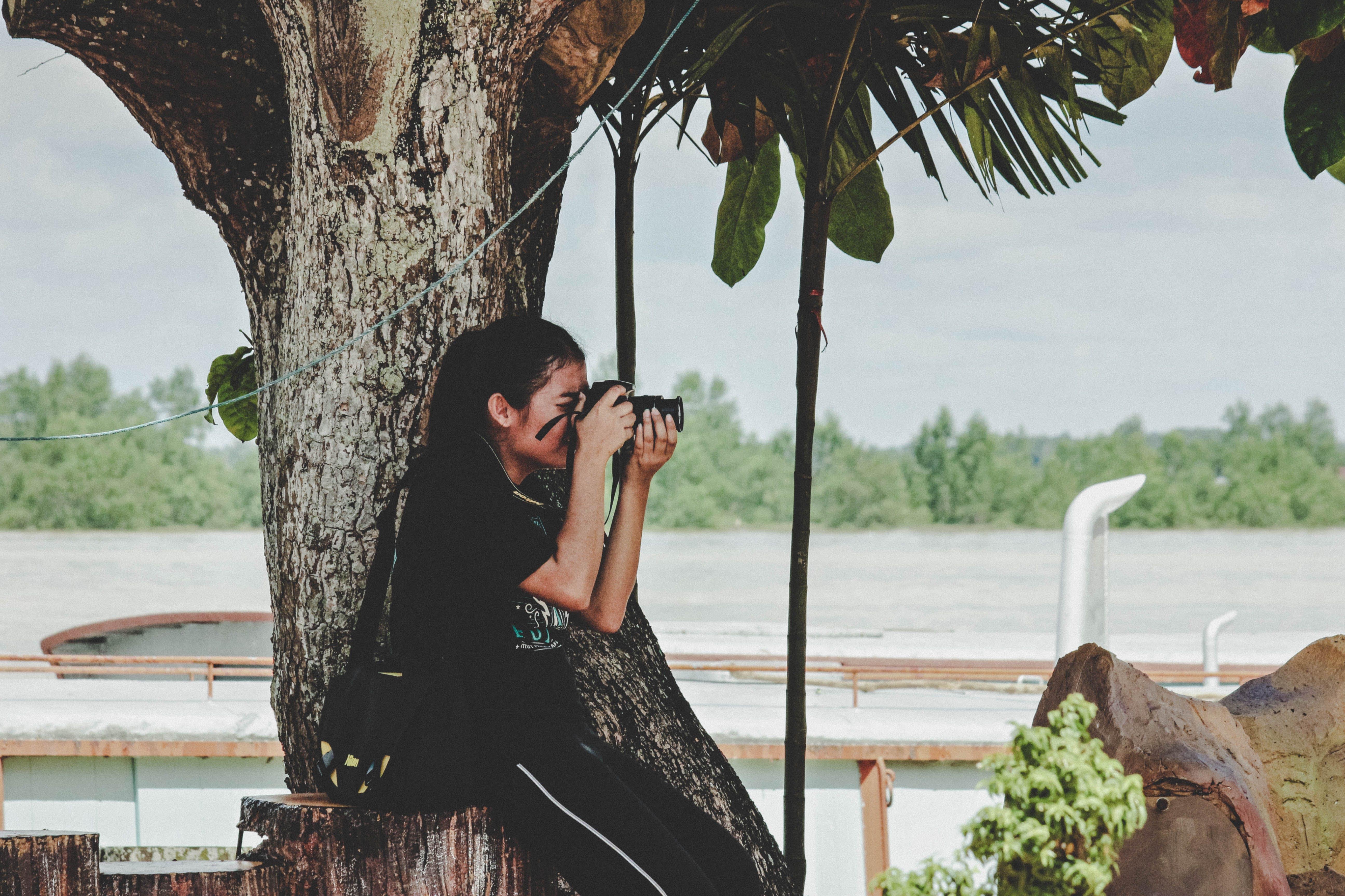 Woman Taking Photo Near to Tree