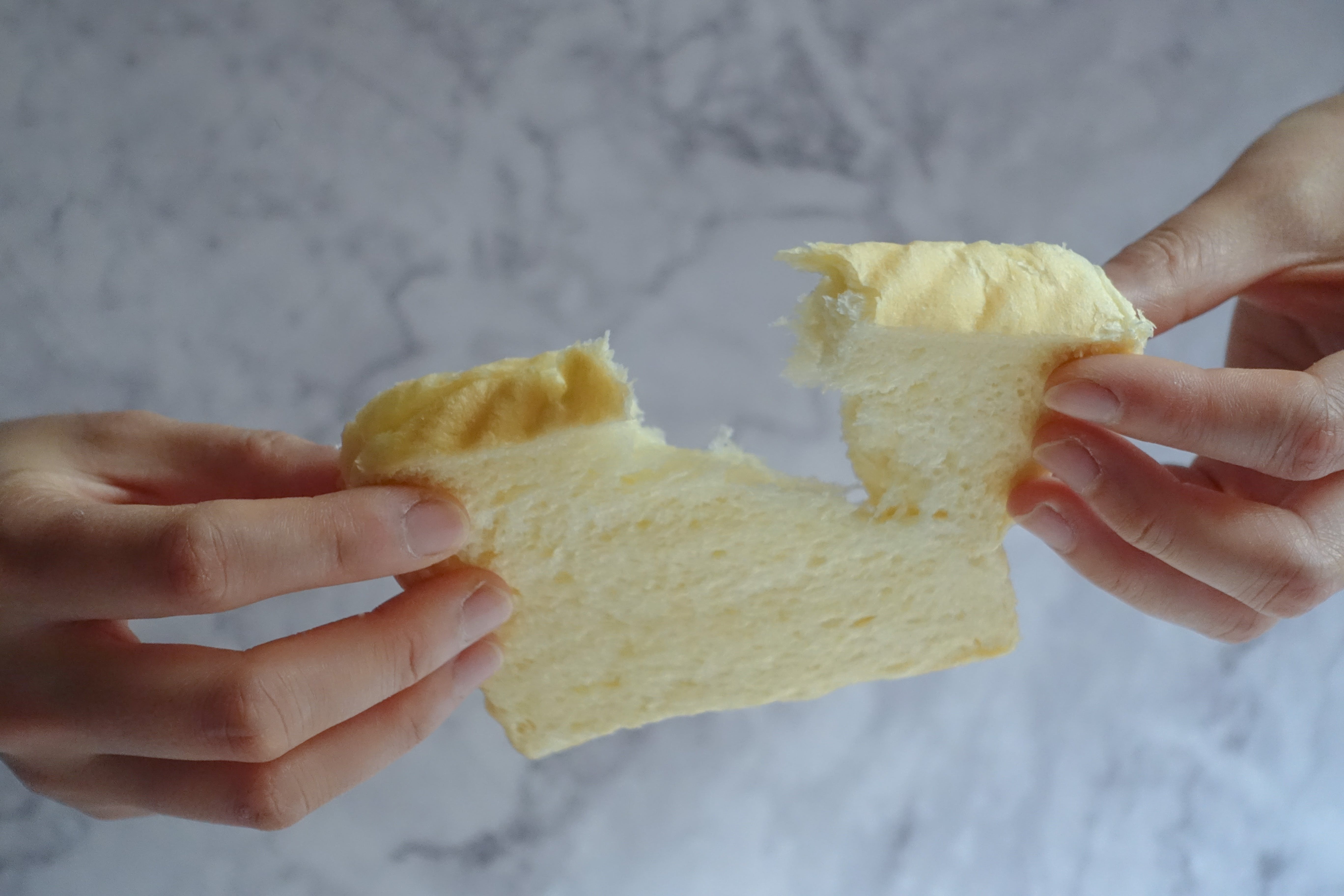 Person Holding Slice of Loaf Bread