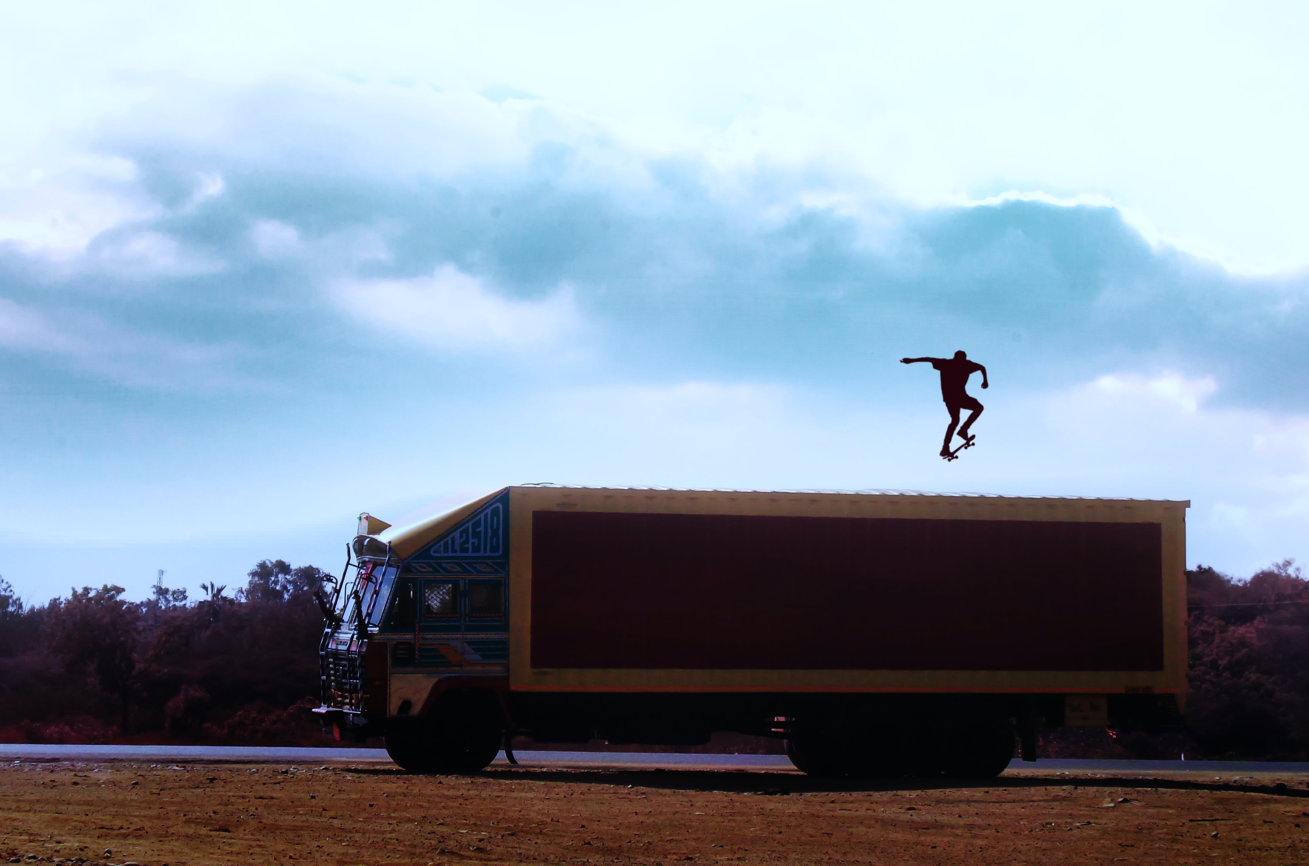 Brown Truck With Man With Skateboard on Top