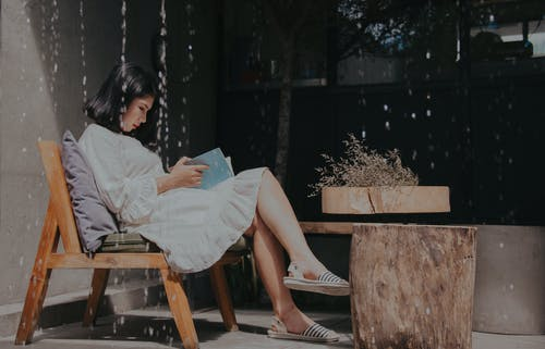 Photography of a Sitting on Chair While Reading Book