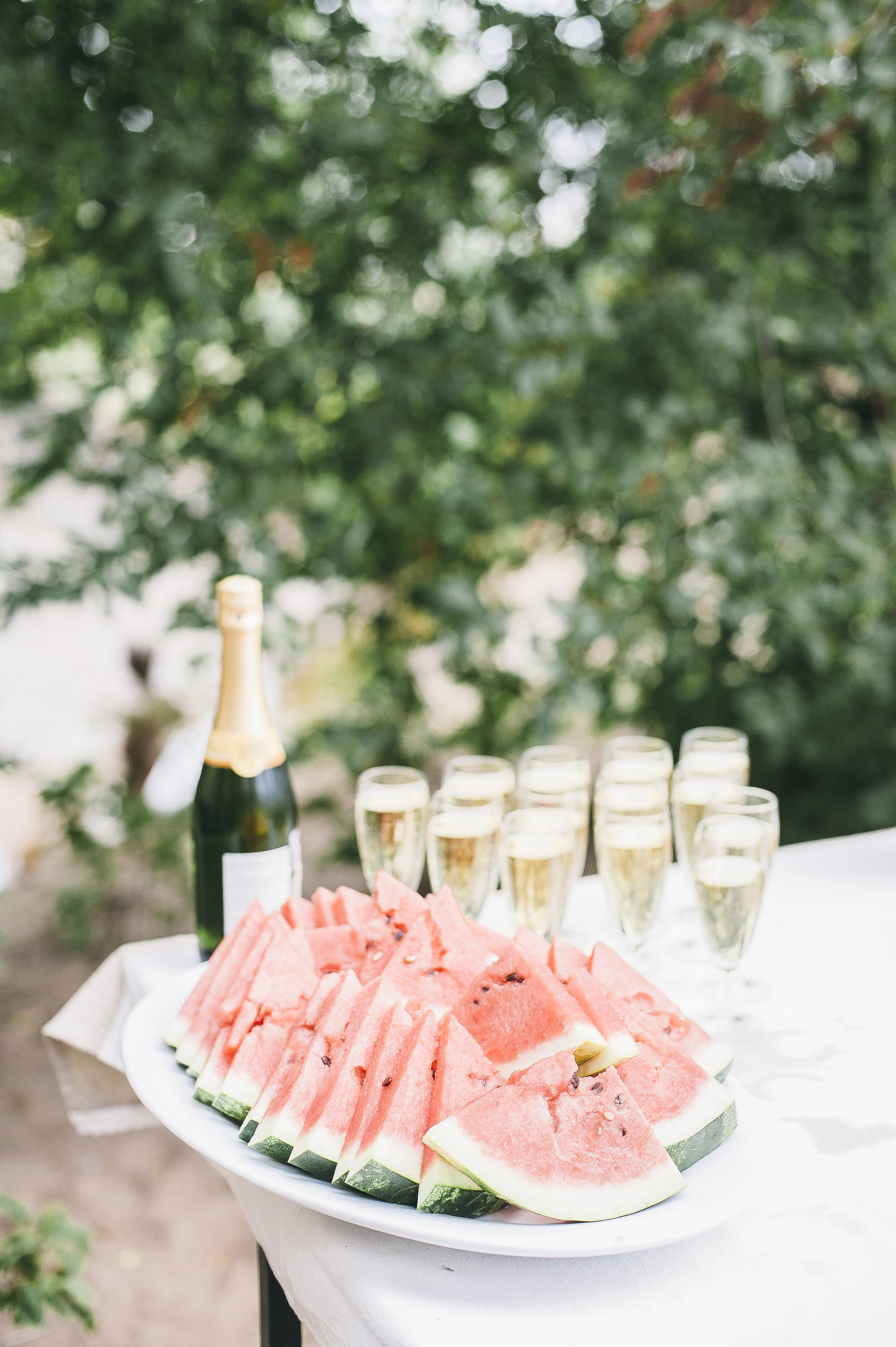 Selective Focus Photo of Bunch of Sliced Watermelons in White Bowl Near Champagne Bottle