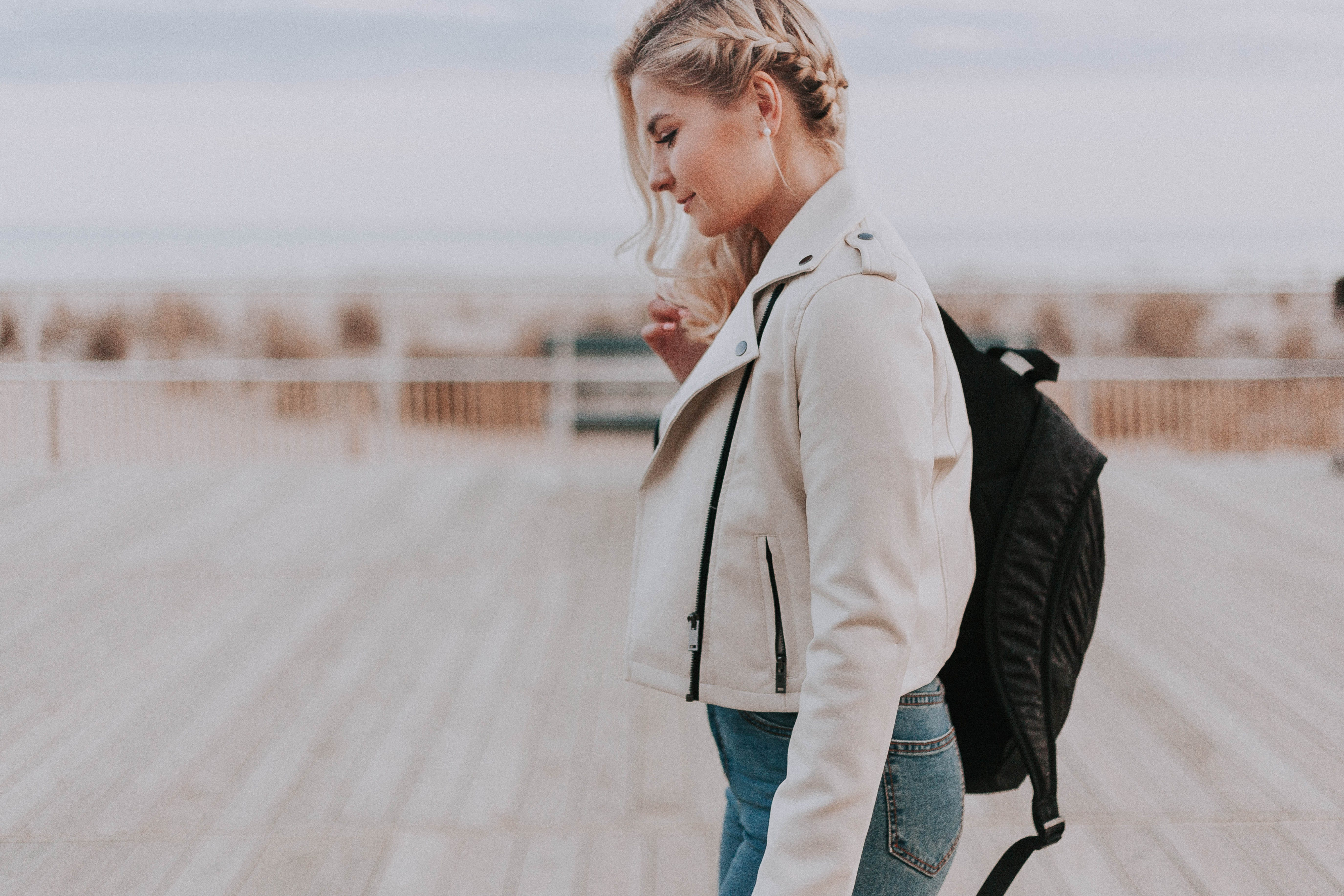 Woman in Black Zip-up Jacket With Black Backpack