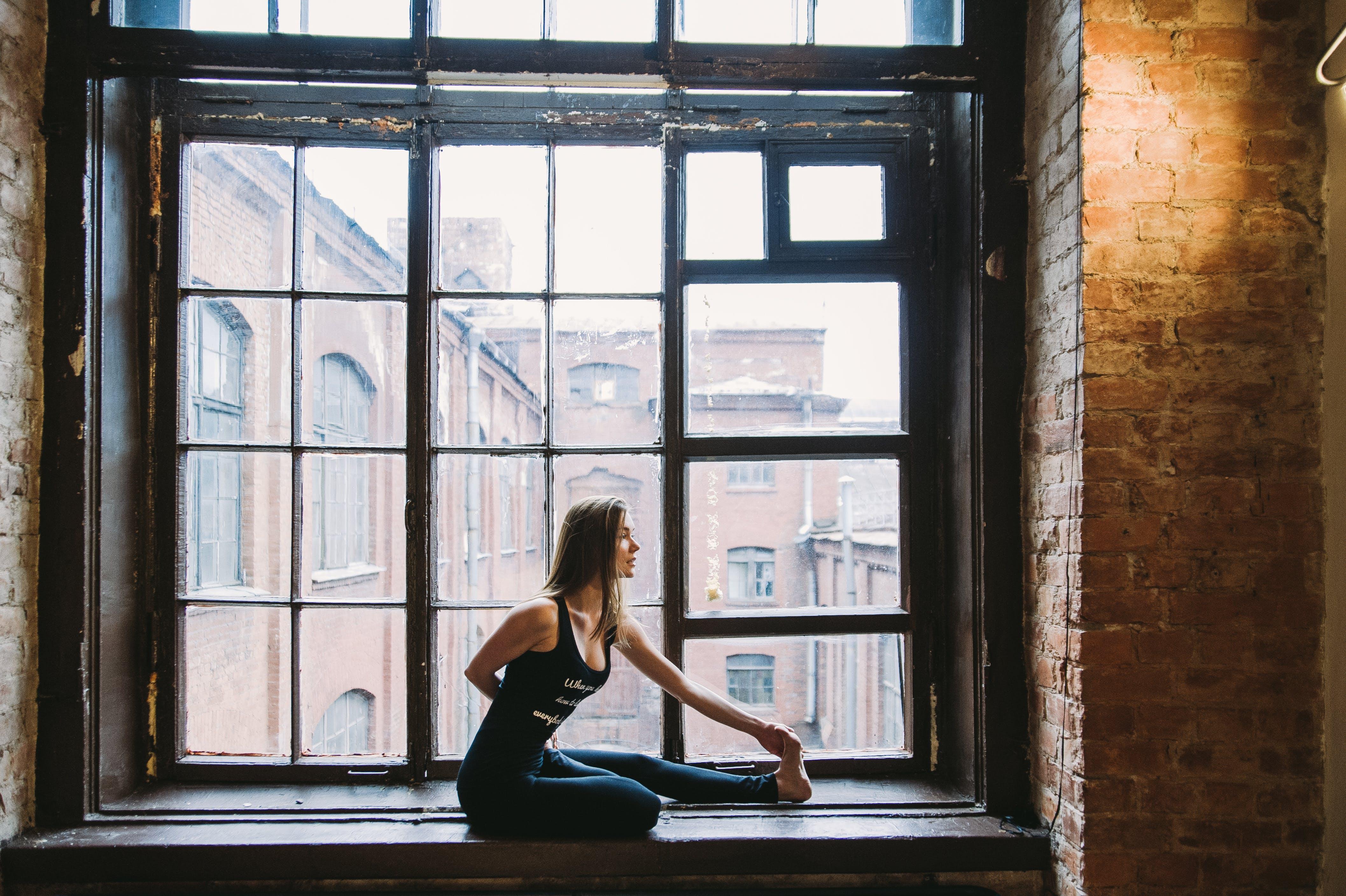 Woman Stretching Beside Window