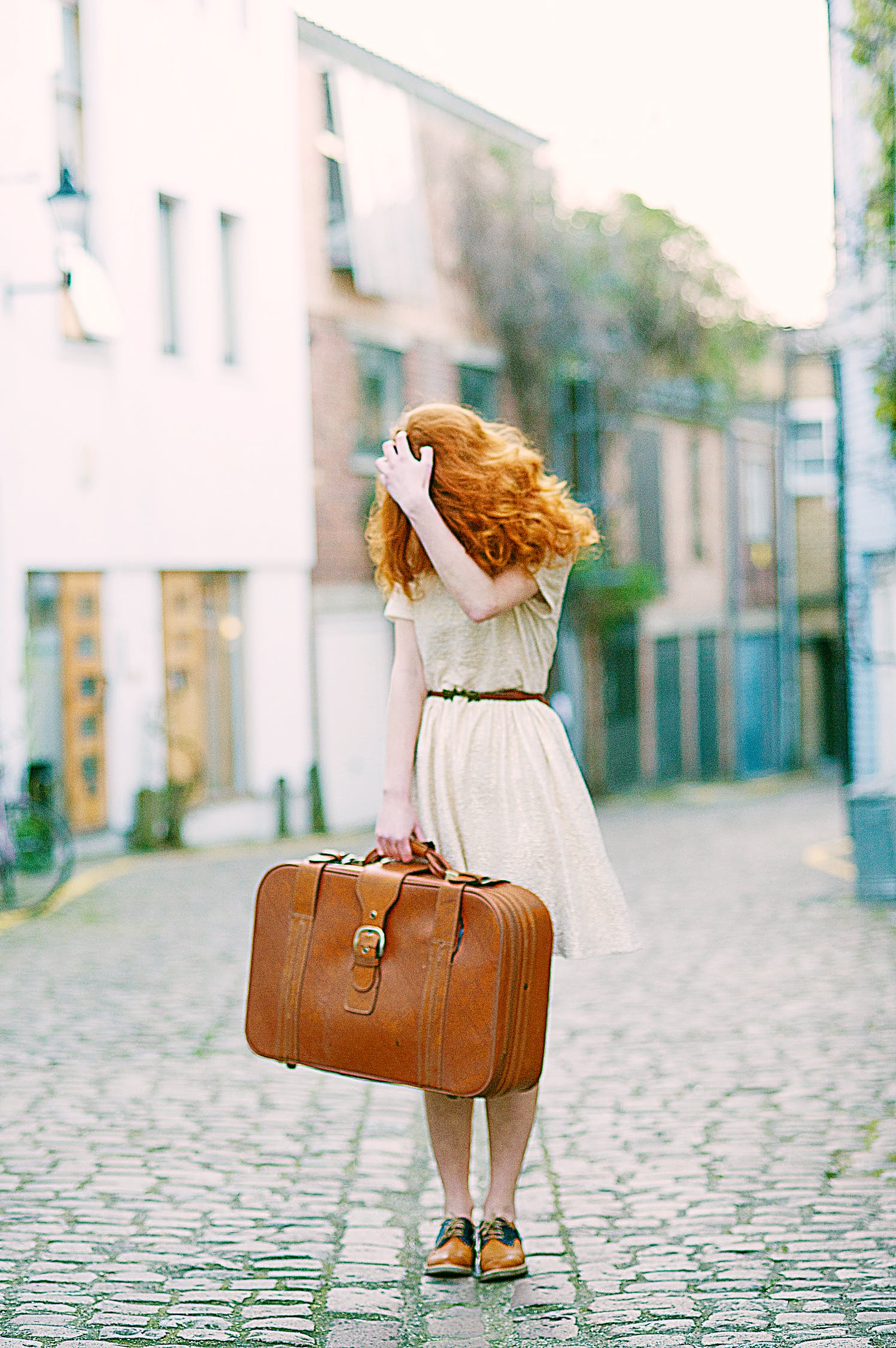 Distraught redheaded woman with a suitcase.