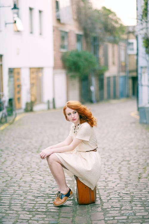 Woman Wearing White Dress Sitting On Brown Lugagge