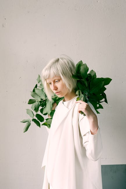 Photography of a woman holding green leaves