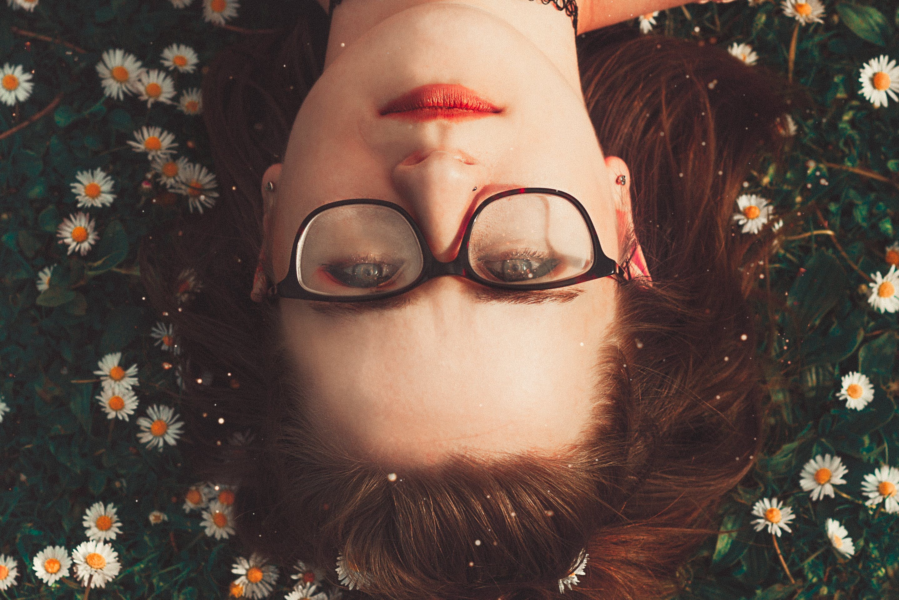 Woman Wearing Eyeglasses Lying On Grass
