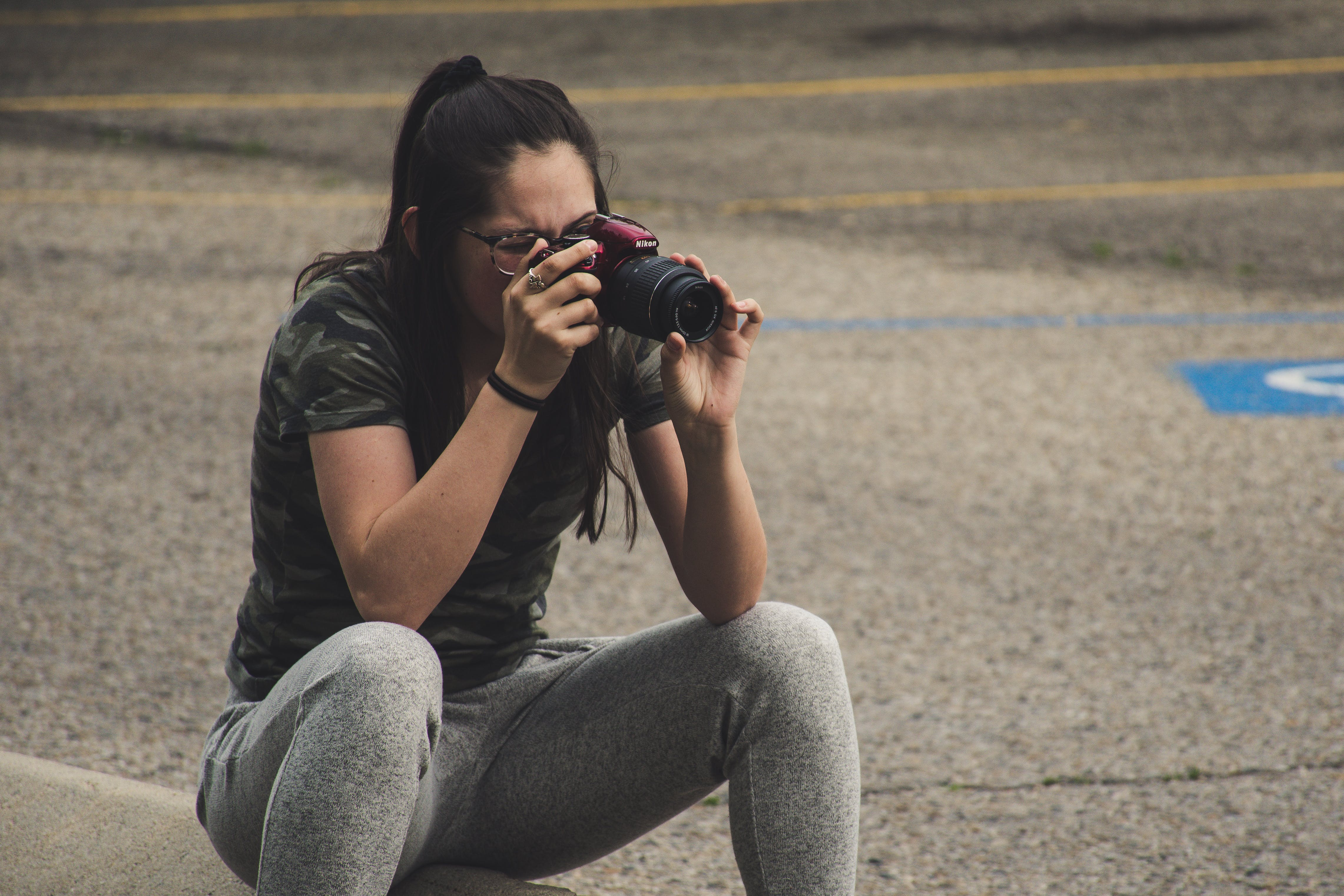 Woman in Gray Pants Sitting While Taking Photo