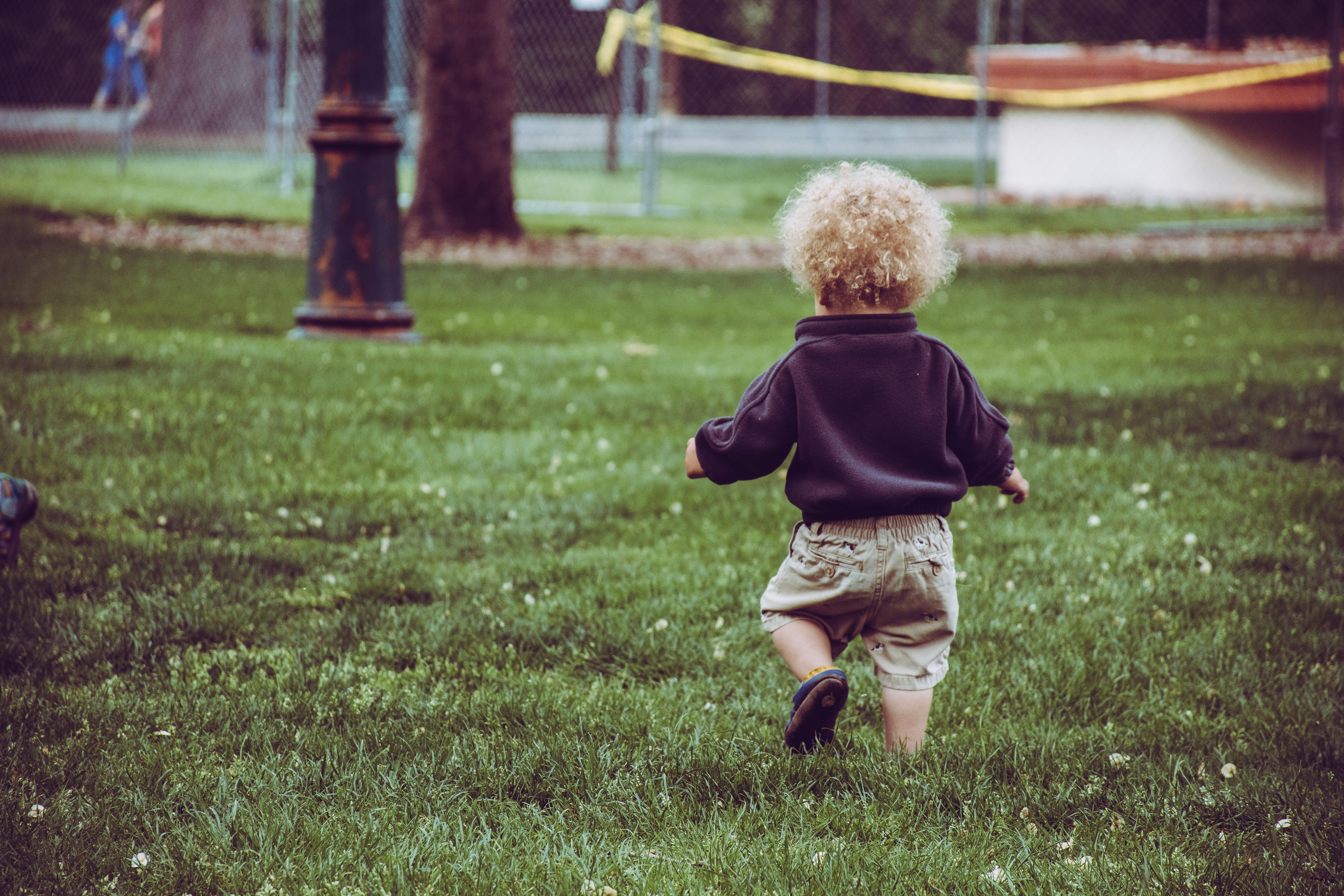 Boy Wearing Brown Shorts Standing on Green Grass