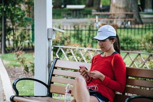 Woman In Red Long-sleeved Top Sitting On Bench