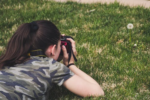 Photo of Woman Taking Photo of Flower on Grass