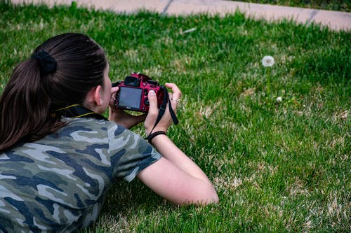 Woman in Camouflage T-shirt Holding Dslr Camera