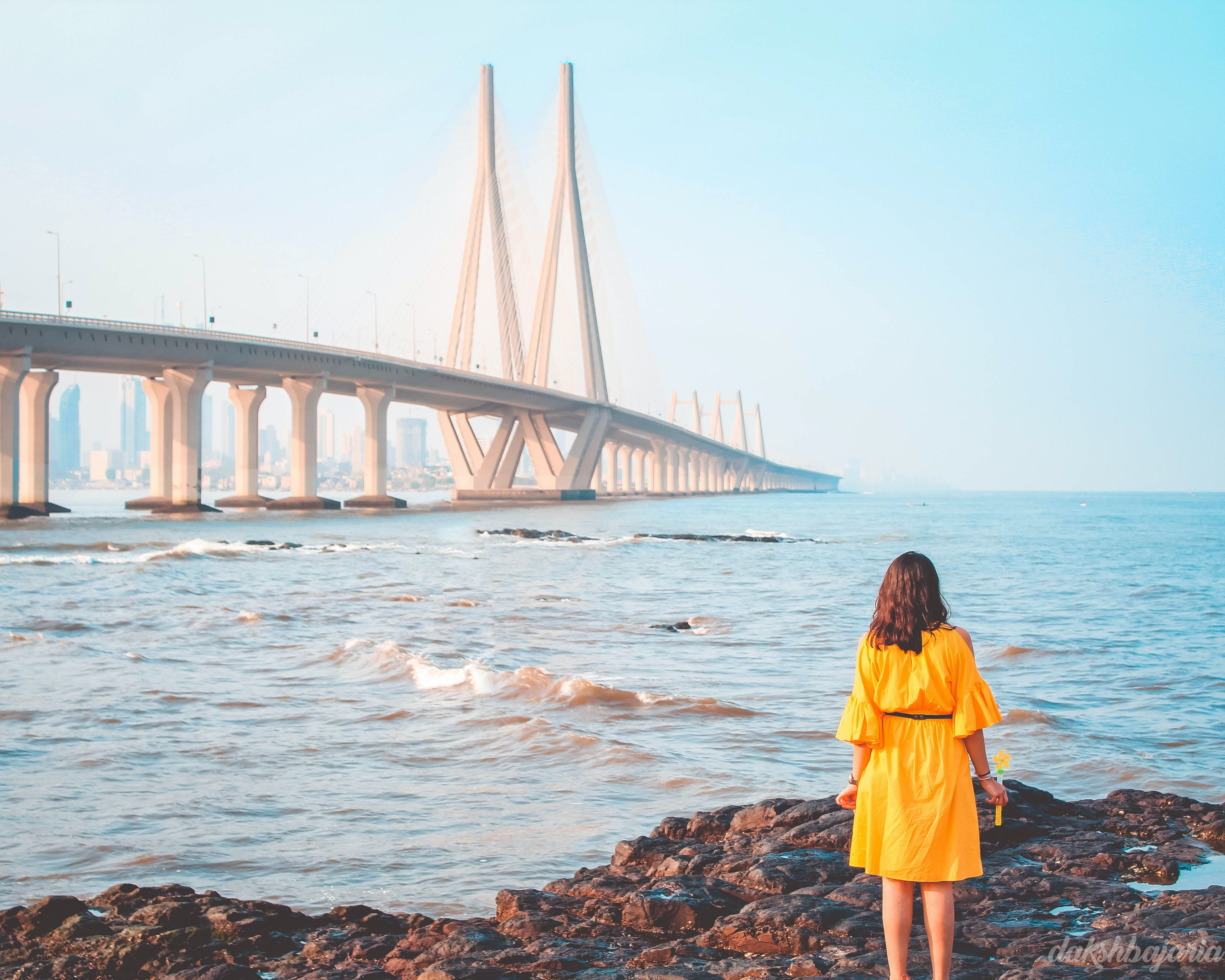 Woman Standing Near Body of Water and Bridge