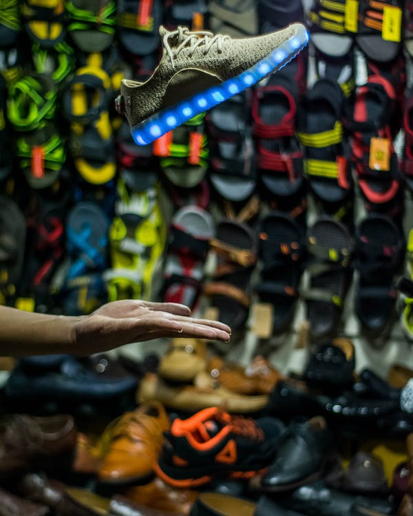 Person Hand Near Assorted Footwear