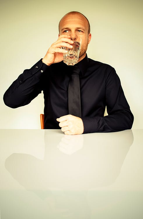 Man in Black Dress Shirt Sitting in Front of White Table Drinking Water