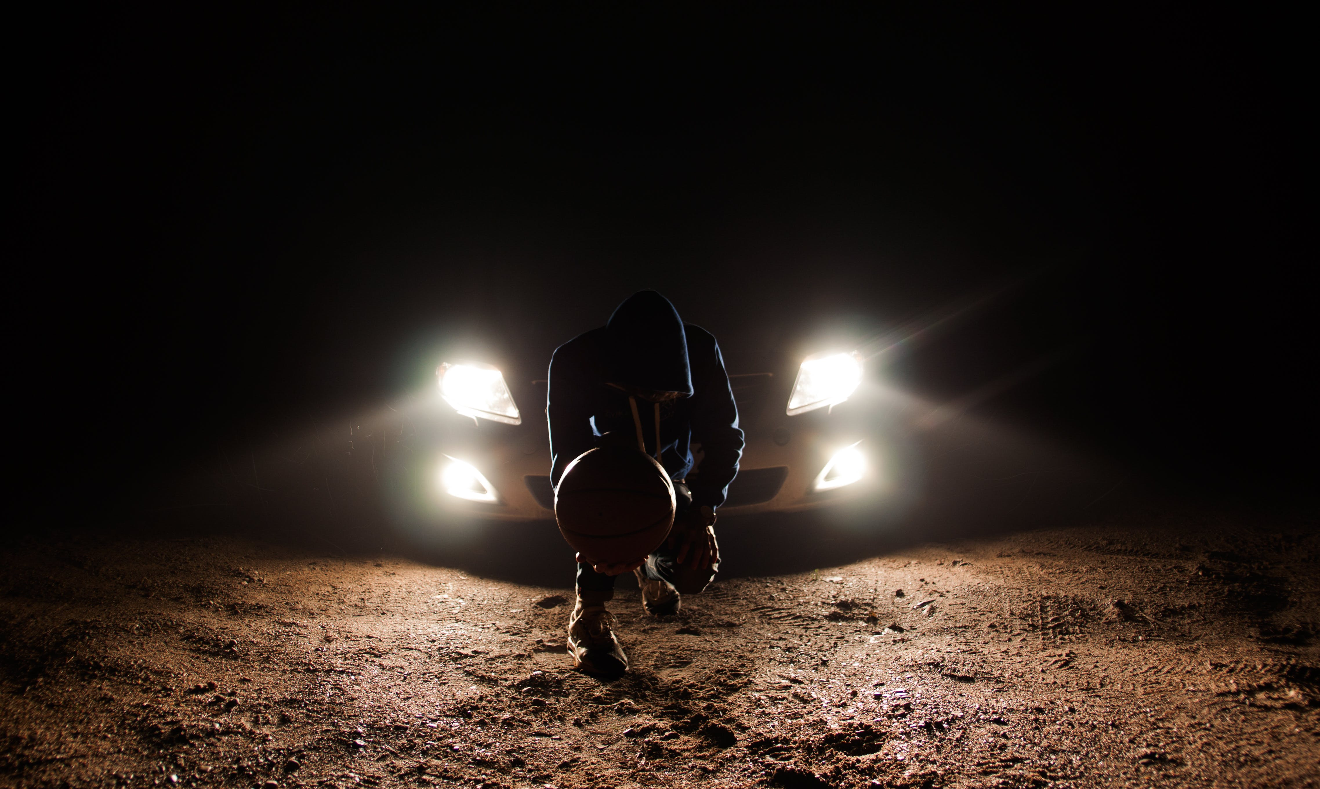 Man Against the Vehicle Headlight Squatting Holding Ball
