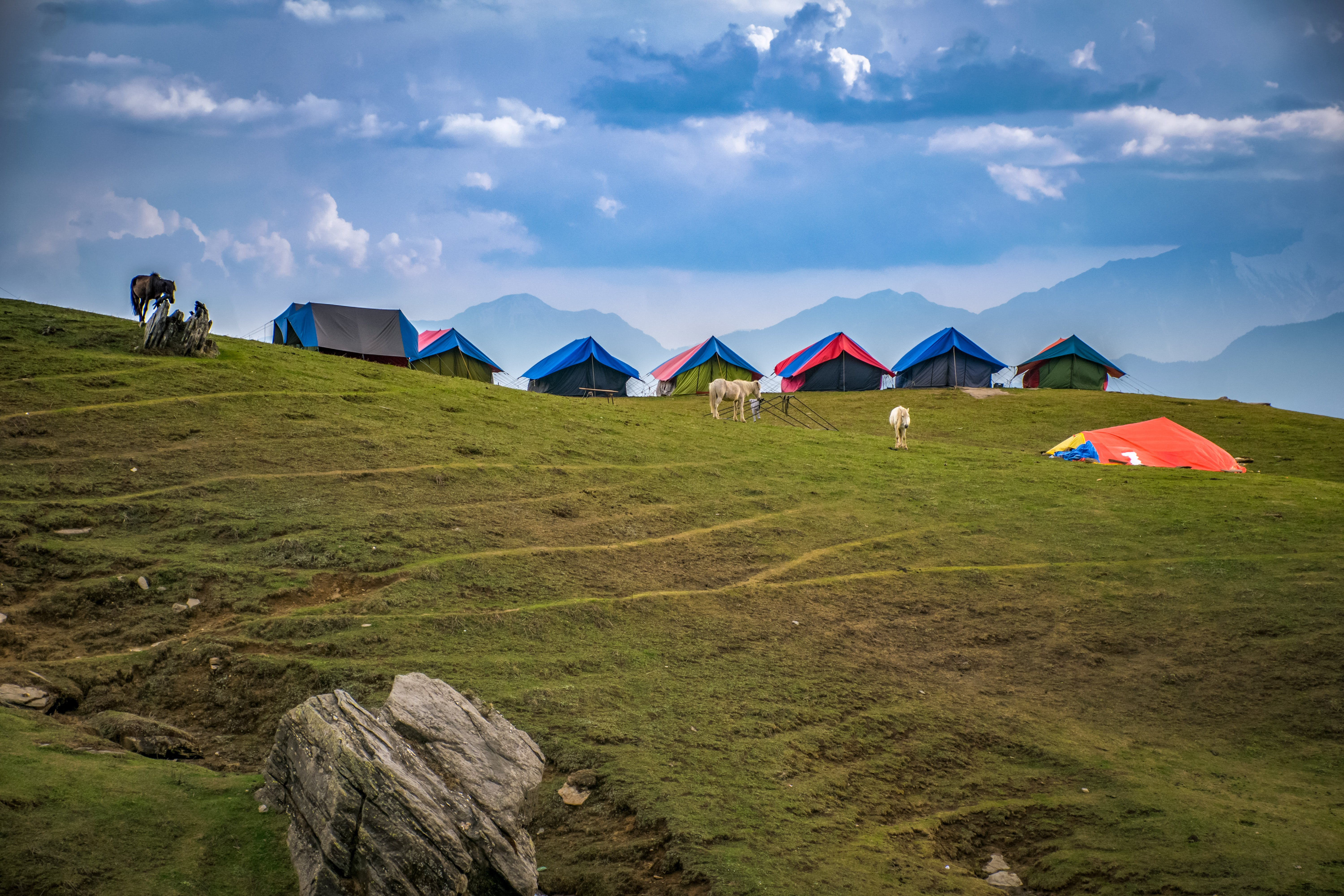 Photographed of Lined Tents on Green Grass Hills