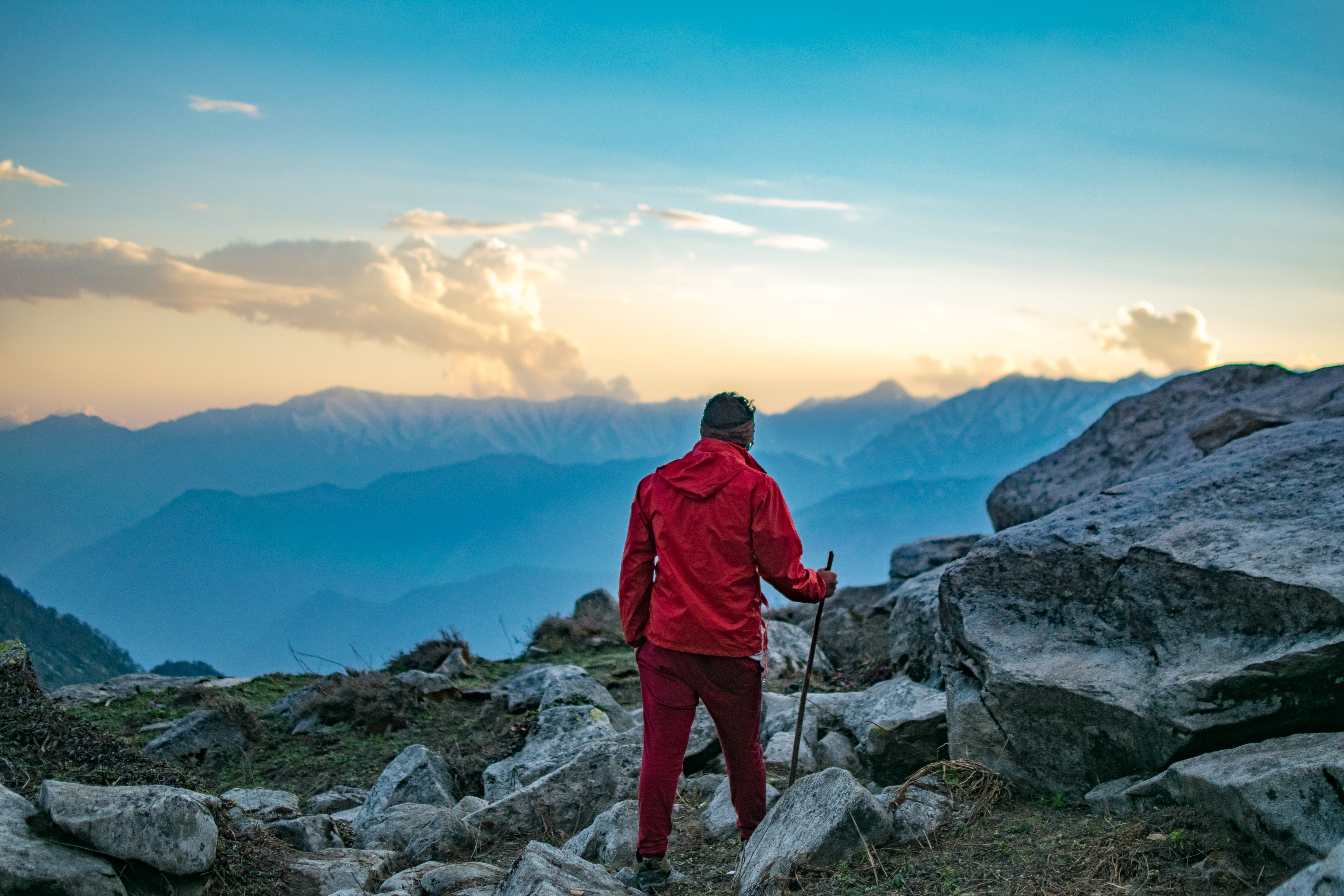 Person Wearing Red Jacket and Maroon Pants Holding Stick Walking on the Rocks at Daytime Photography