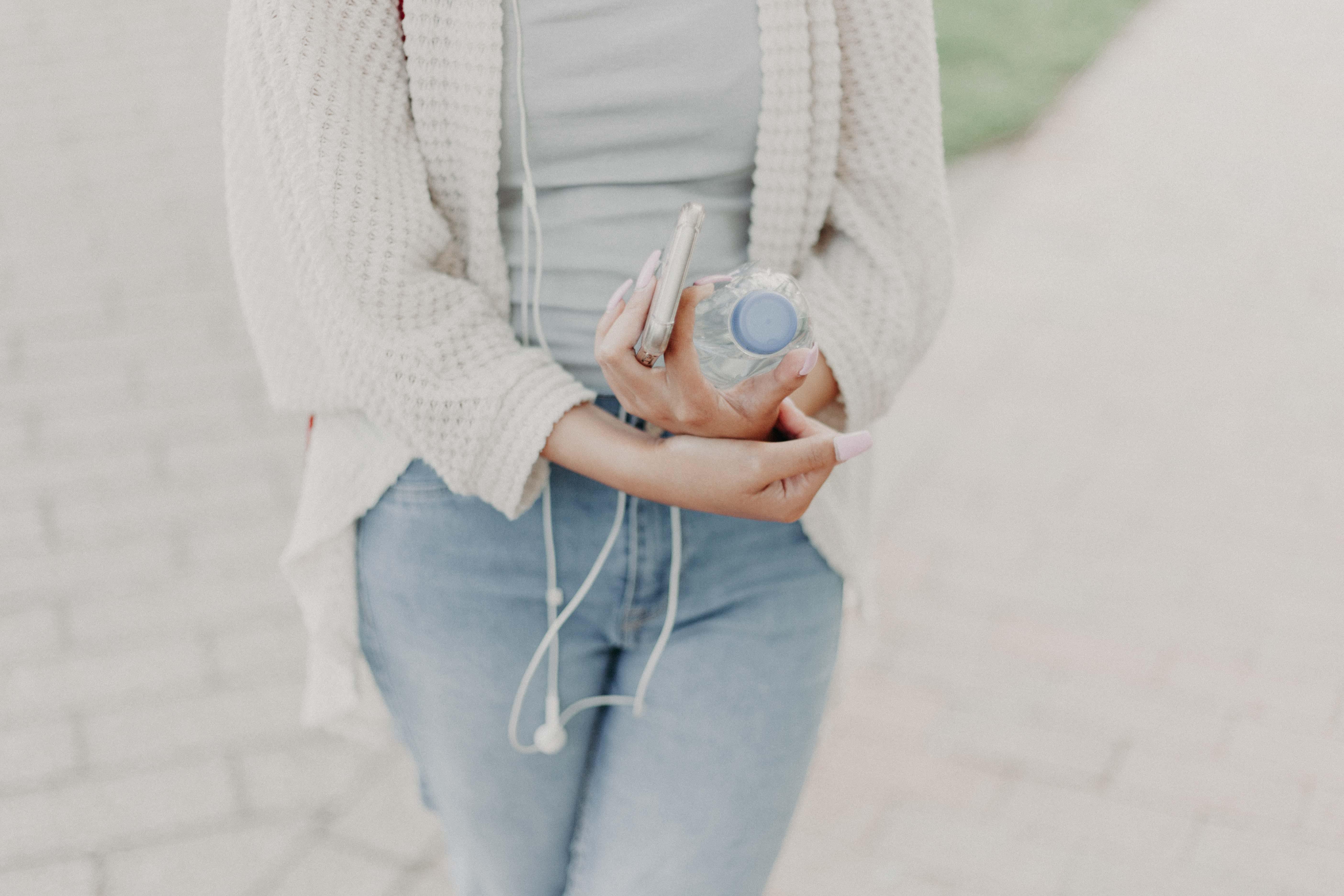 Woman Wearing White Cardigan Holding Plastic Bottle
