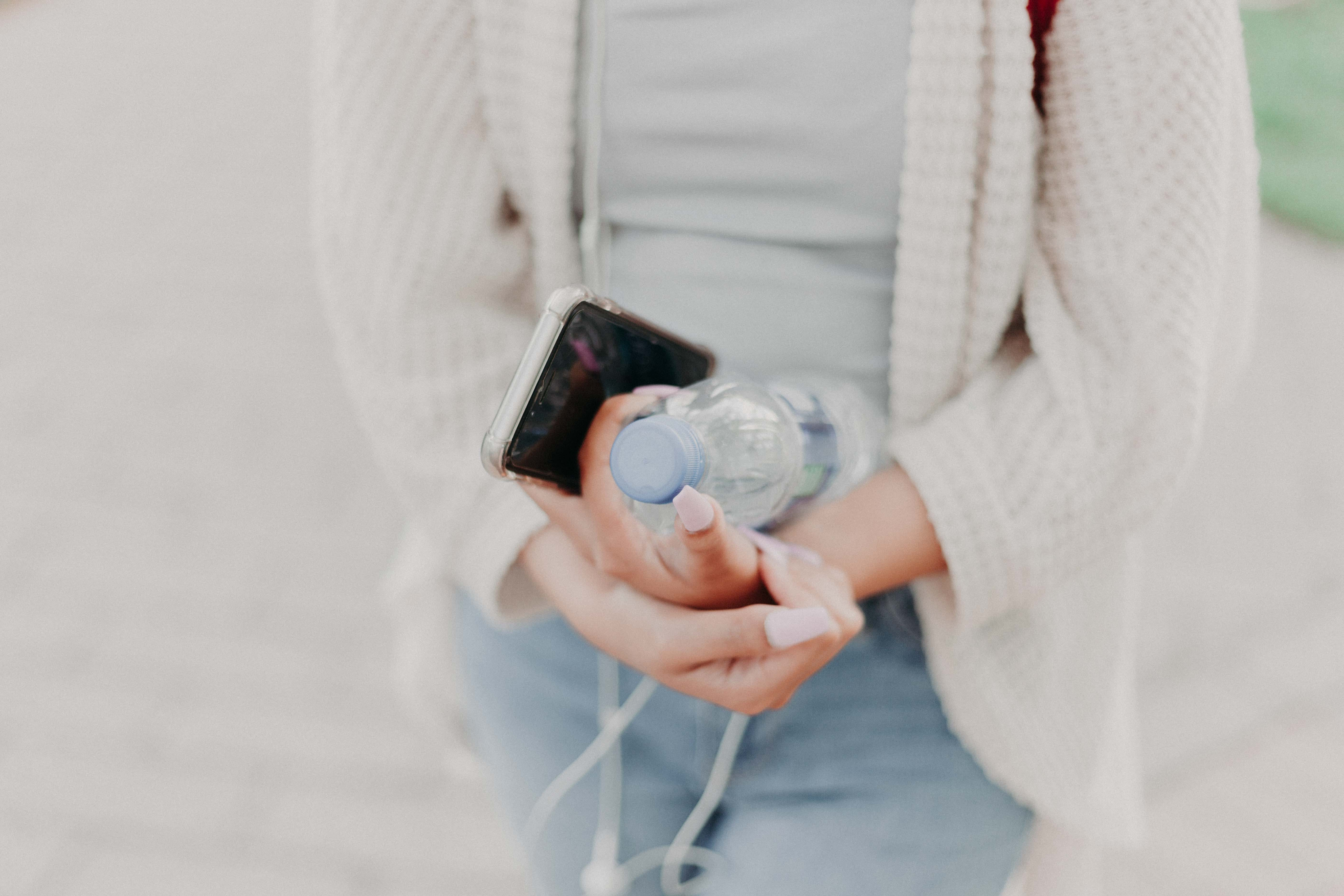 Selective Focus Photography of Woman in White Cardigan Holding Water Bottle and Black Smartphone