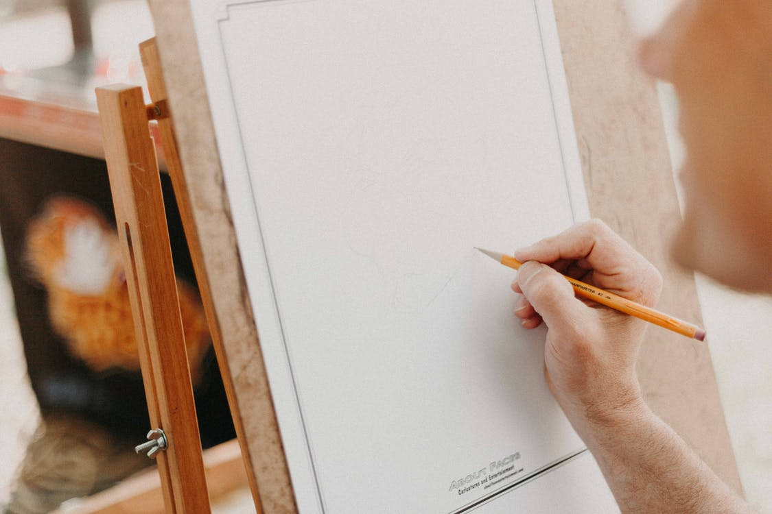 Person Holding Pencil on White Canvas