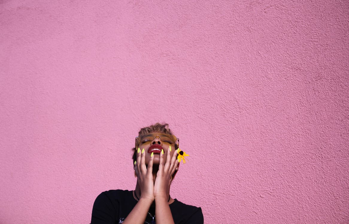Stylish young African American female in casual wear and sunglasses with closed eyes touching face while throwing head back on pink background