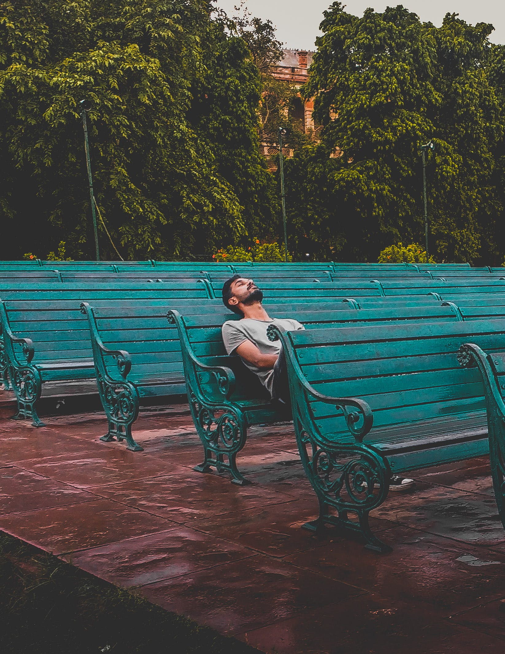 Man Sitting and Closing Eyes on Teal Bench