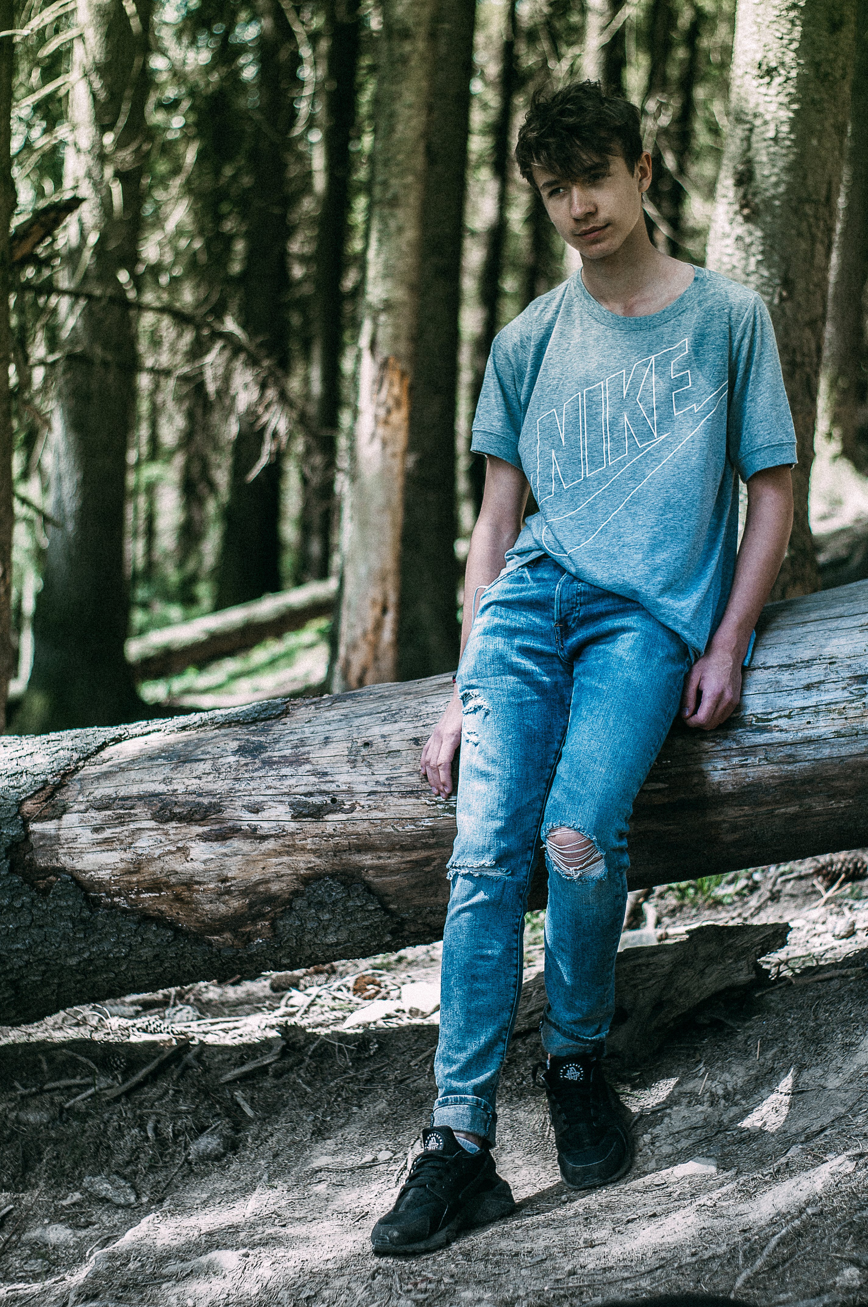 Free stock photo of blue jeans, boots, fallen tree, hairstyle