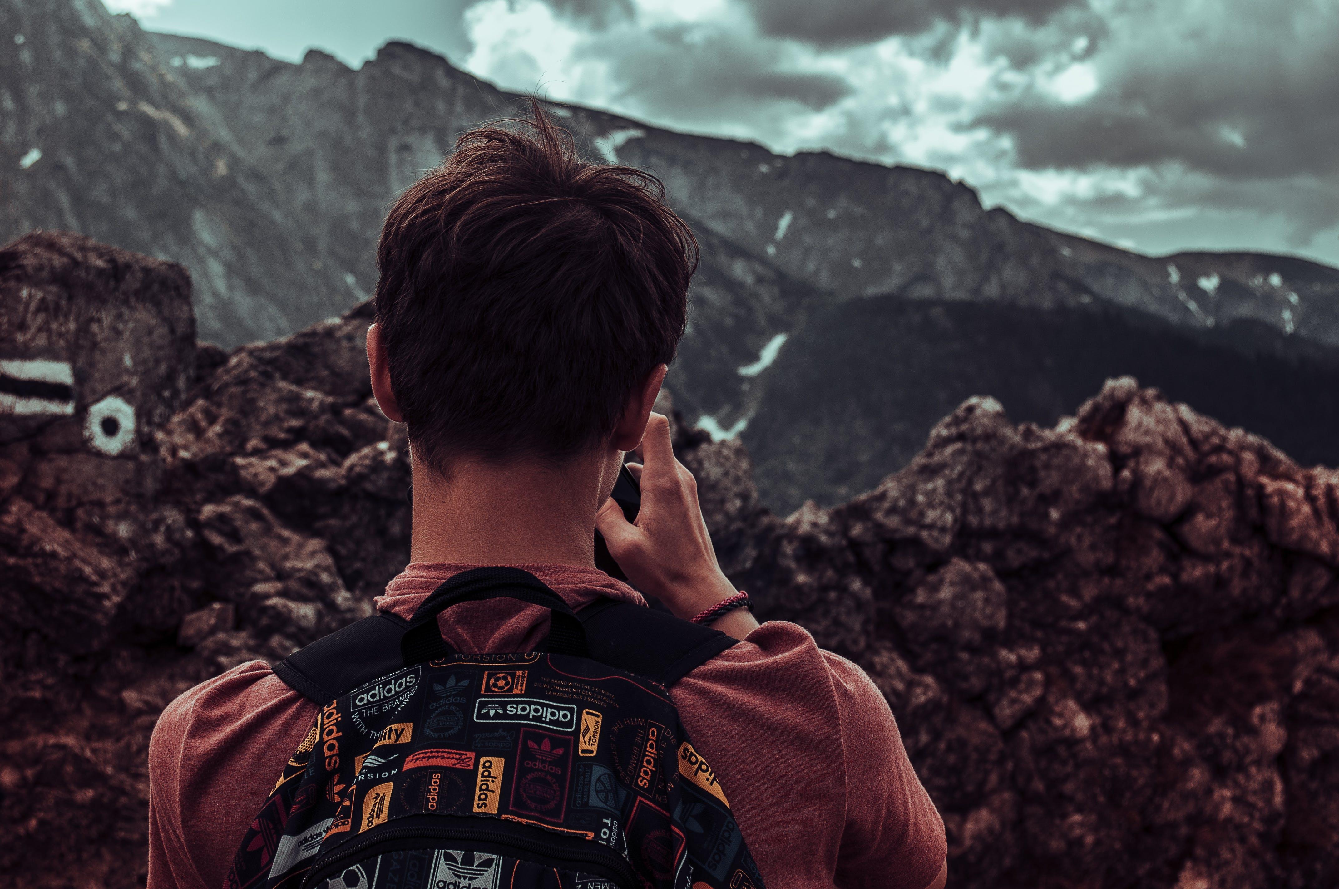 Man Taking Photos Of Mountains